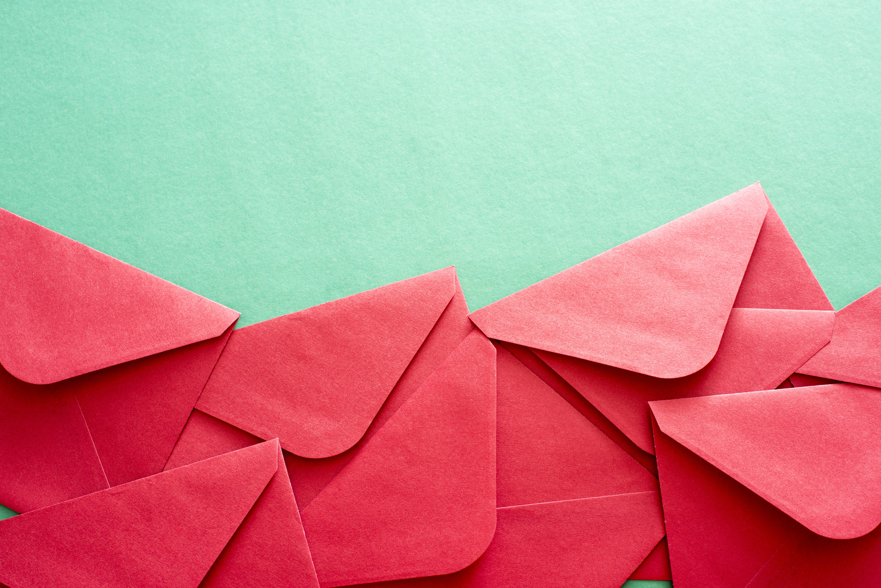 Festive red Christmas or valentines envelope border over a textured green paper background with copy space