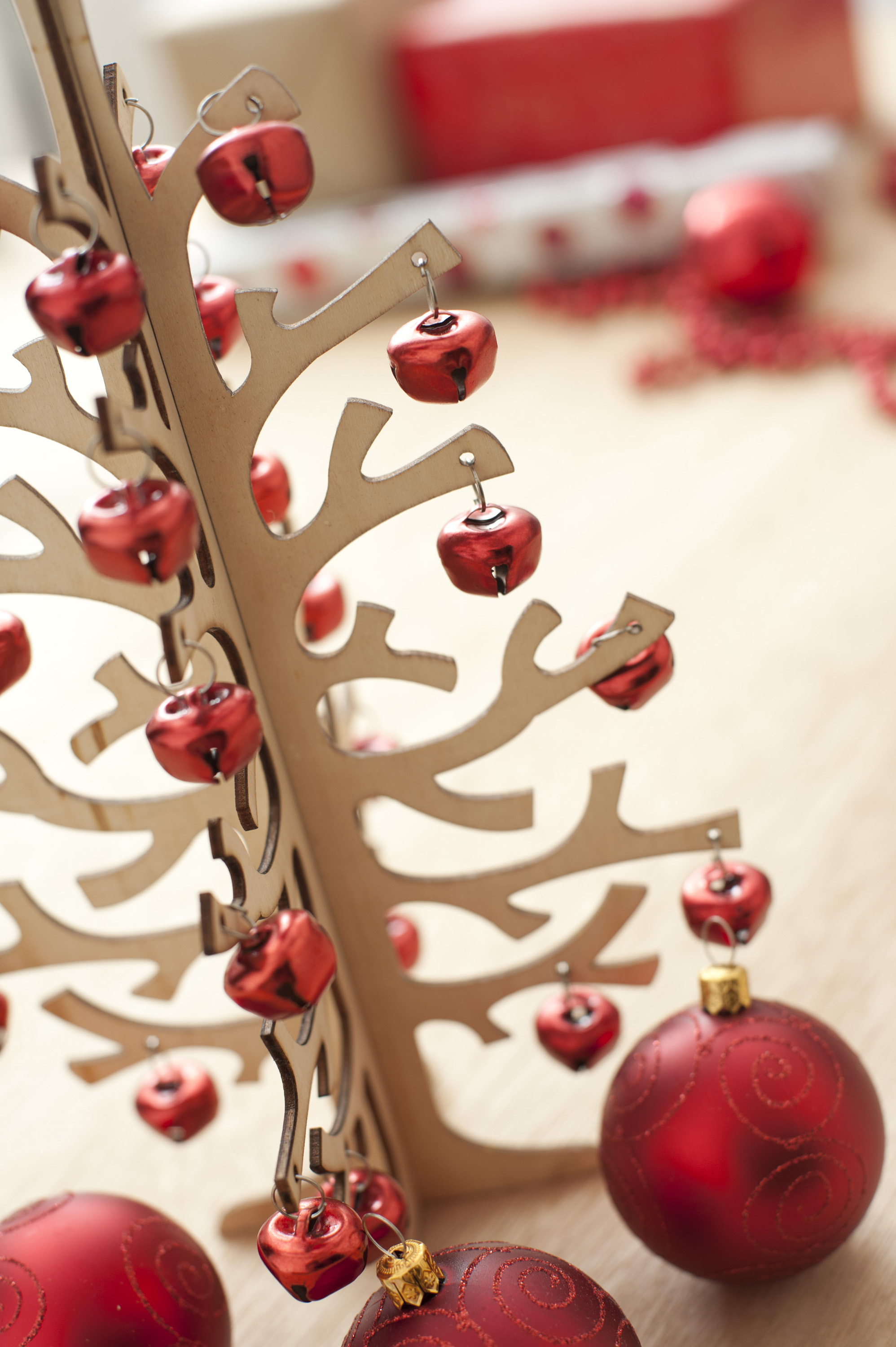 Close-up of wooden Christmas tree decorated with bright red garland