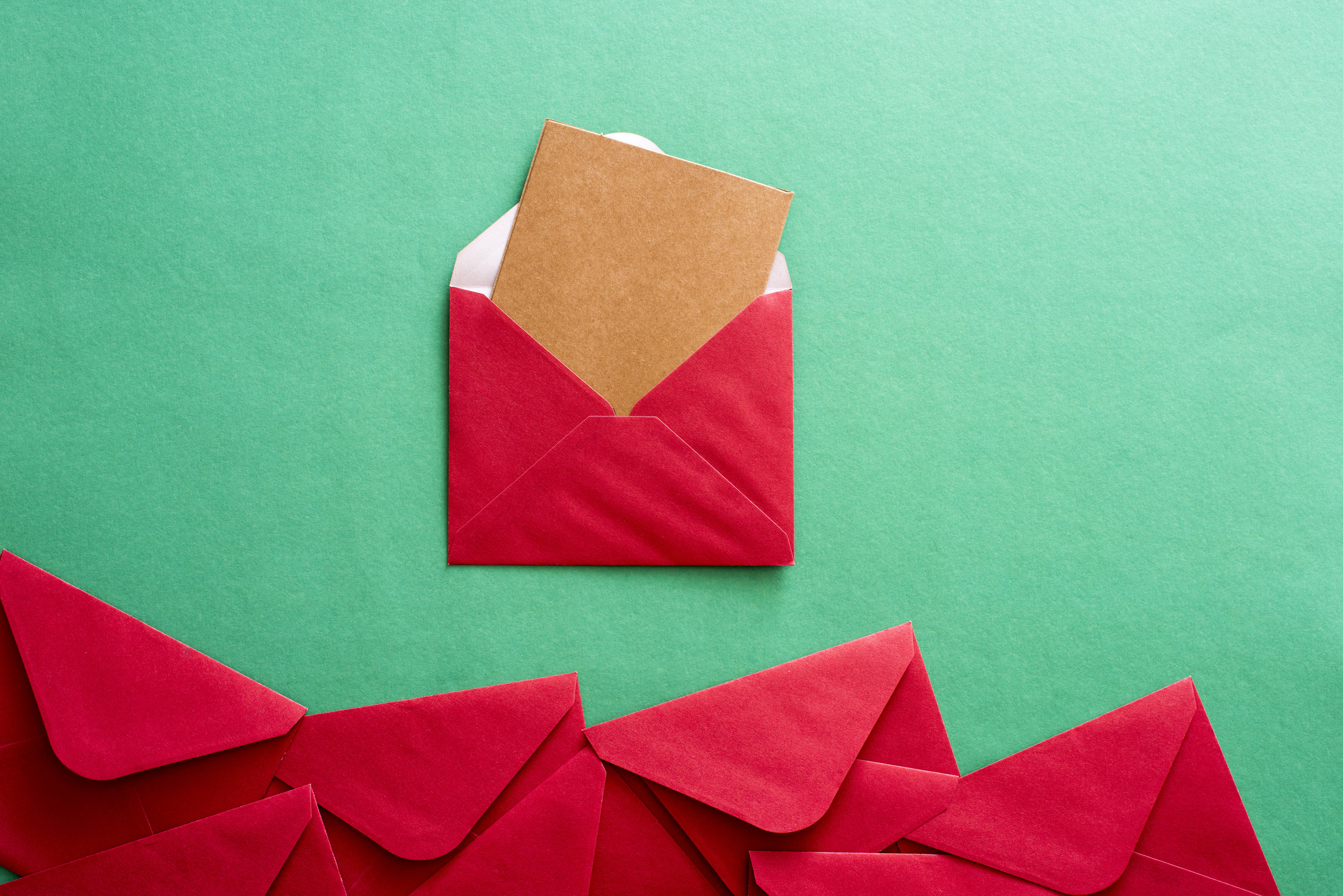 Opened red festive Christmas envelope with a blank brown card protruding from the flap on a green background with a lower border of more red envelopes