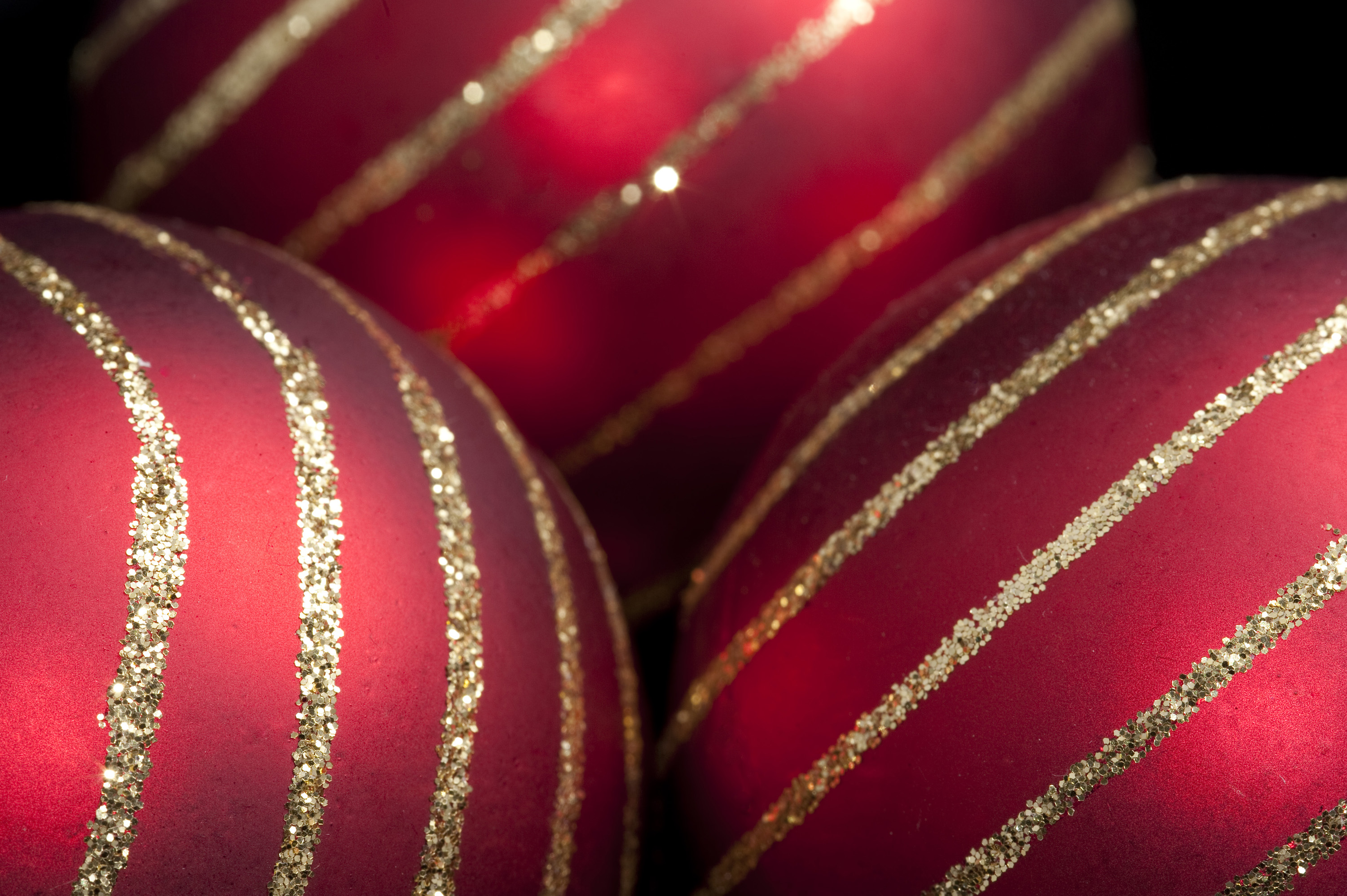 close up on three red christmas baubles with lines of gold glitter