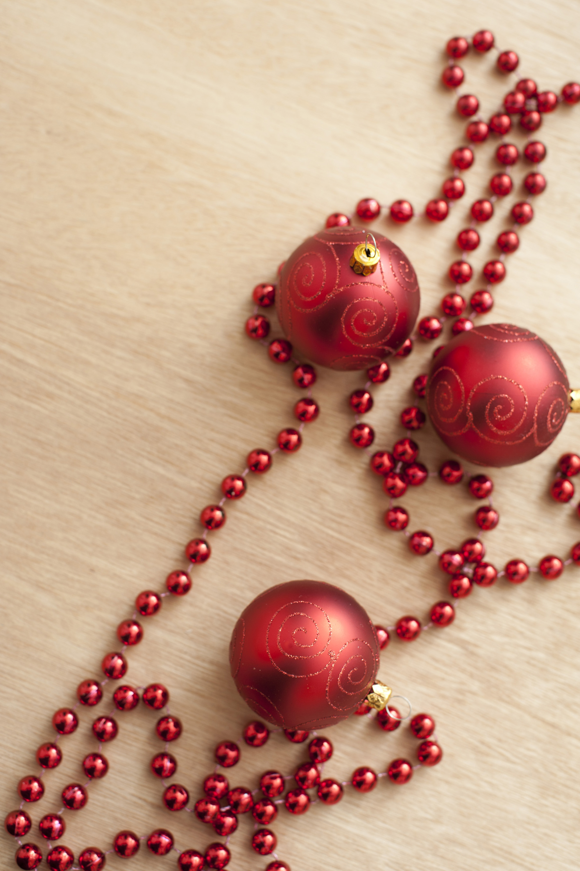 Close-up of three red Christmas balls and red beads on wooden table