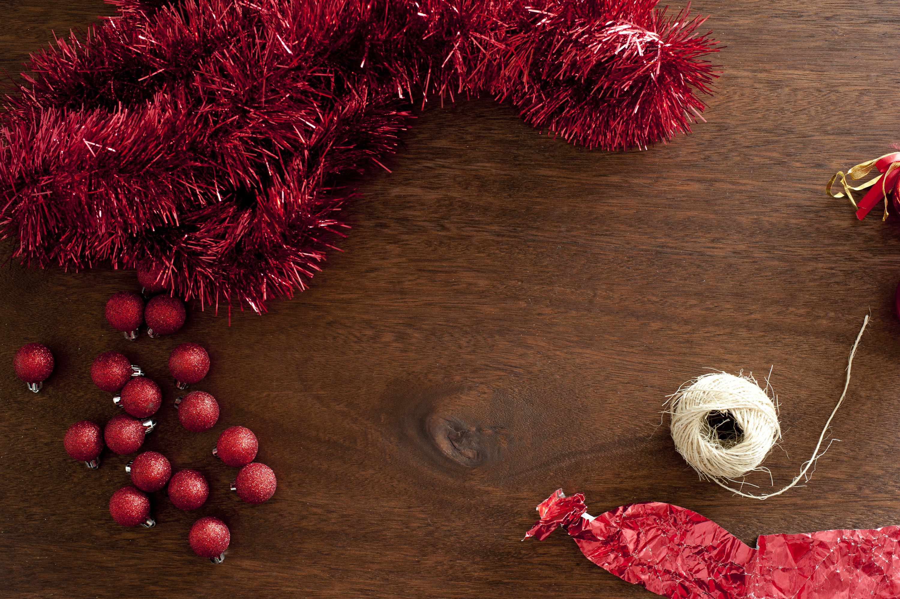Red Christmas decorative elements: rope, glare, wrapping and balls on wooden table. From above