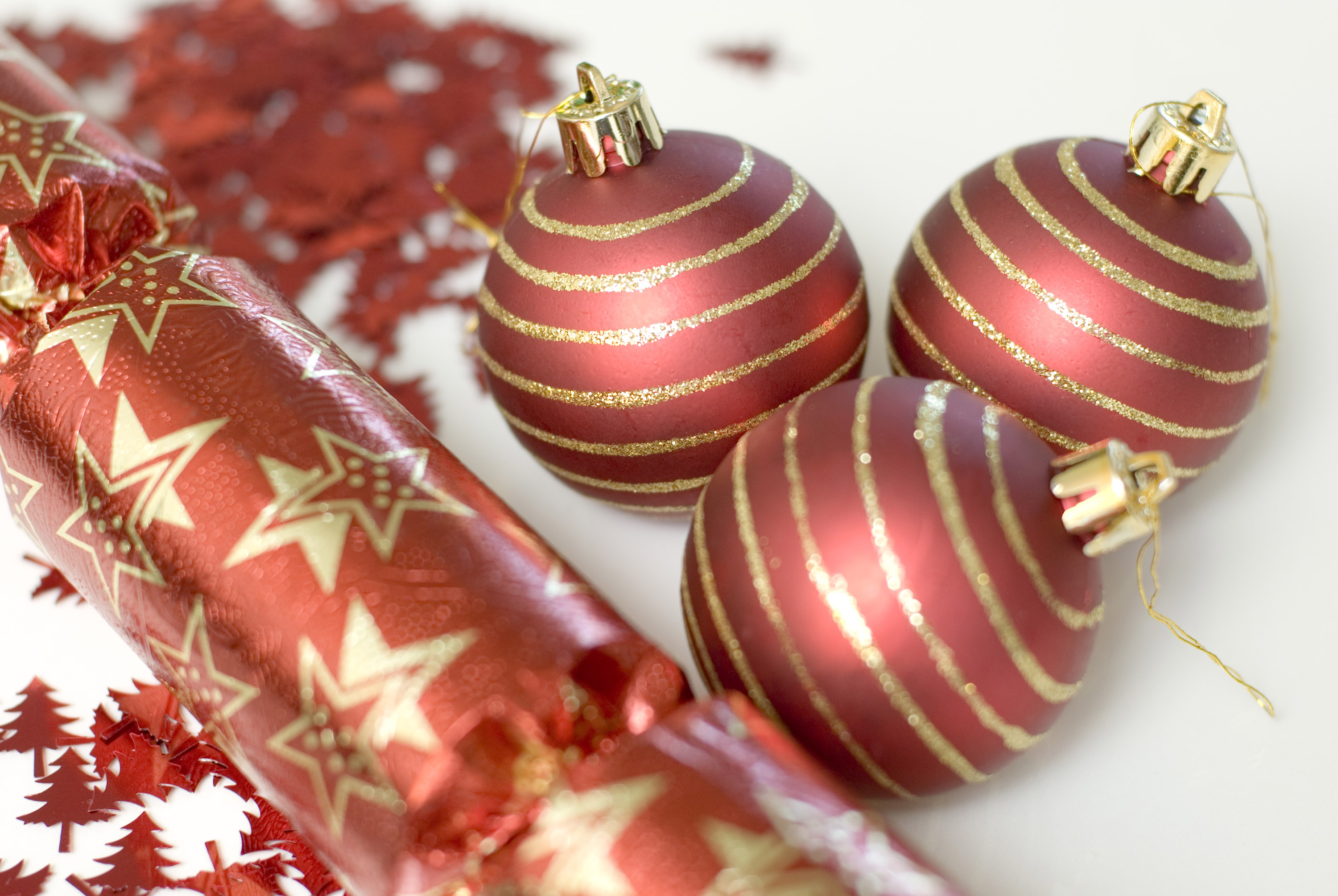 A christmas background composed of three baubles, christmas glitter and a red christmas cracker.