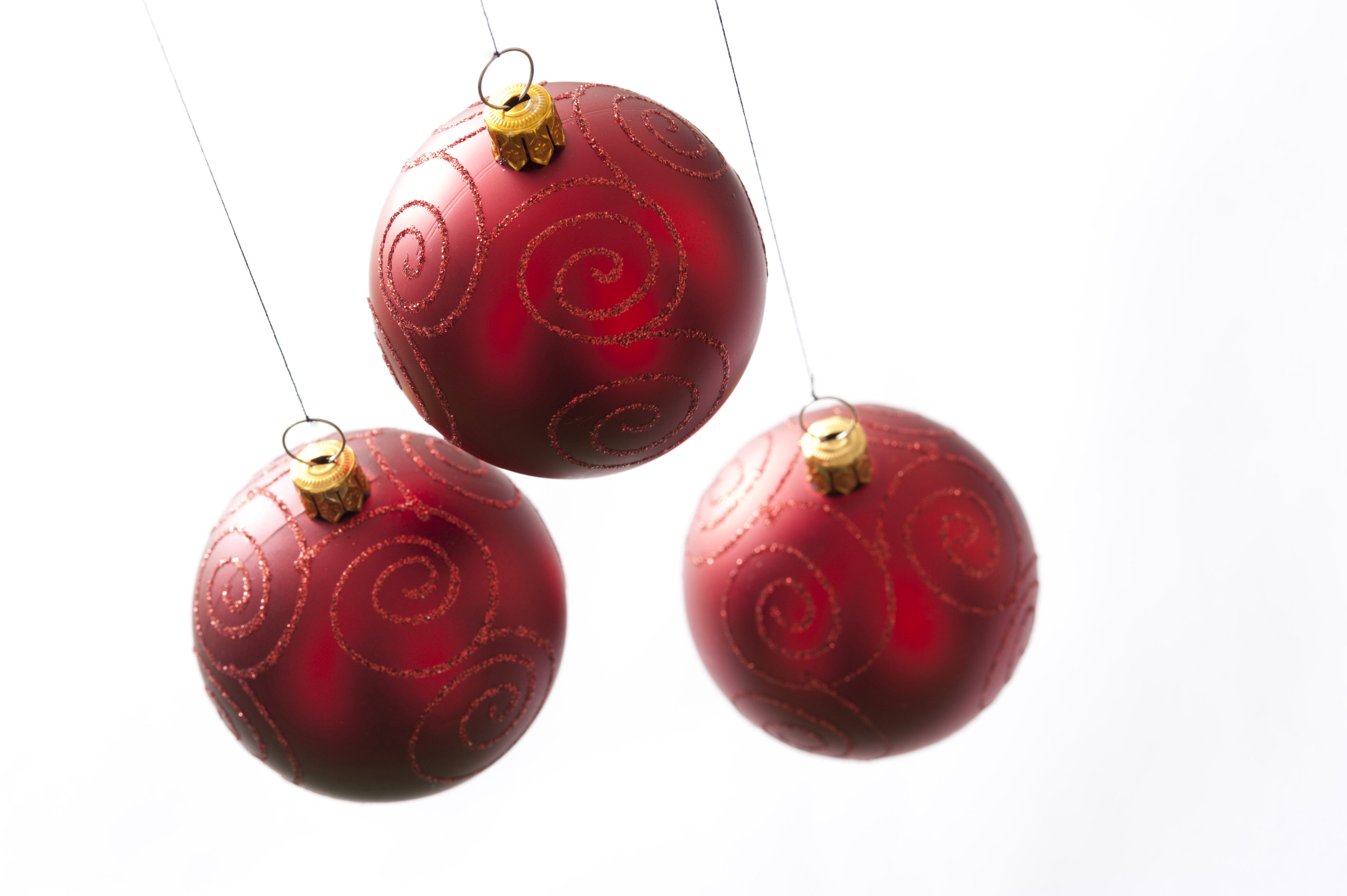 Three red Christmas balls hanging on white background. Isolated