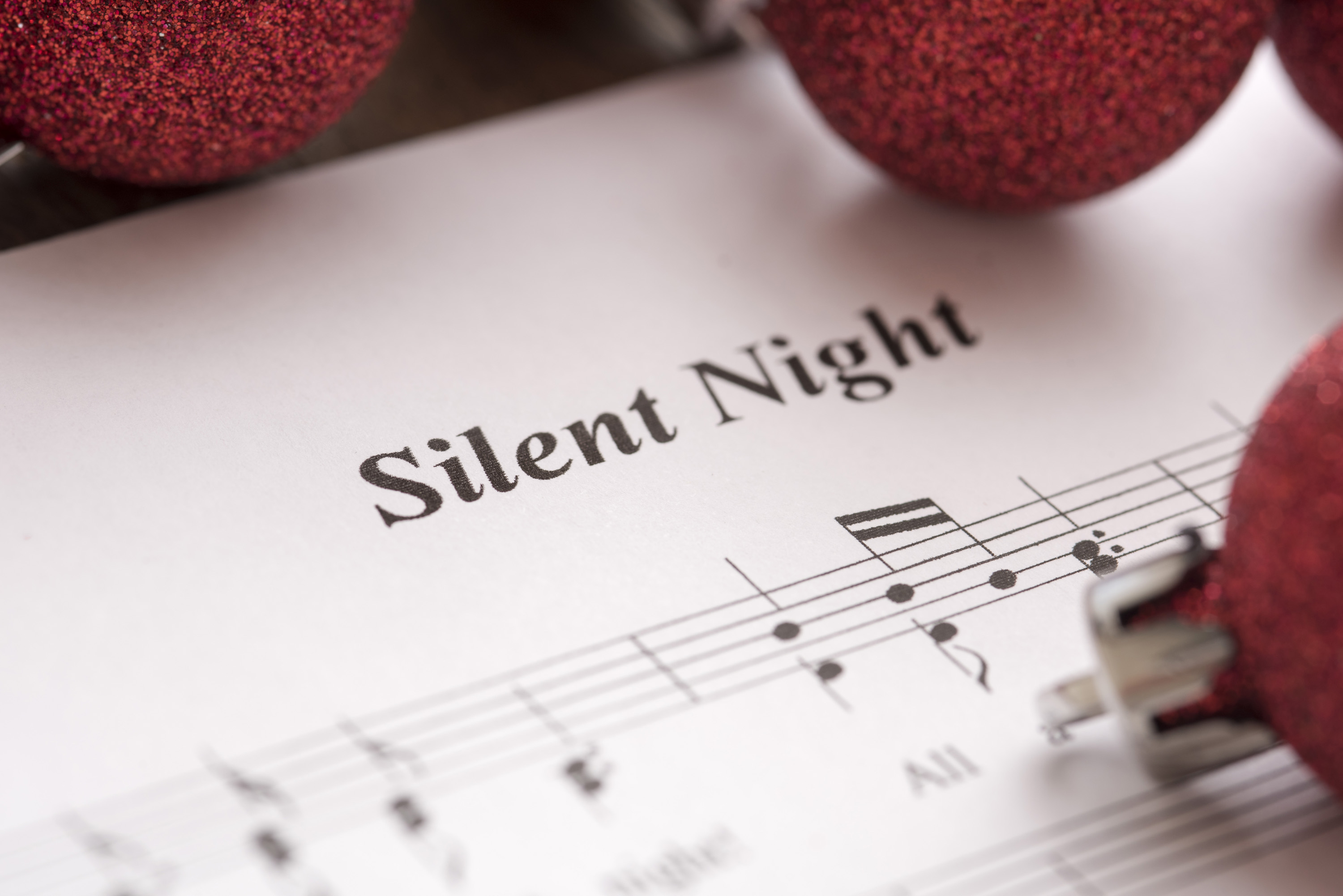 Silent Night music score background with festive red Christmas baubles in a close up view
