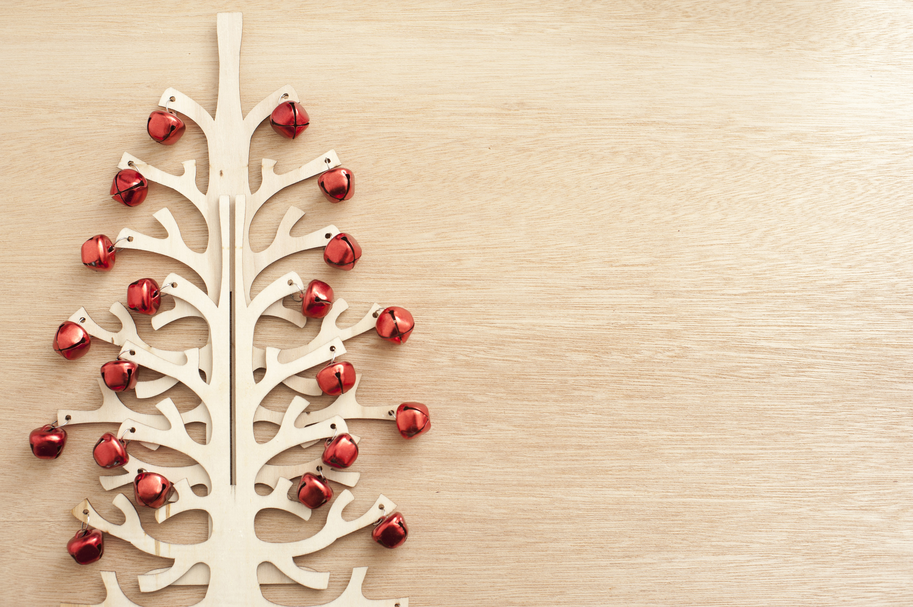 Modern festive decorations, a wooden tree decorated with red Christmas balls lying on wooden table. From above