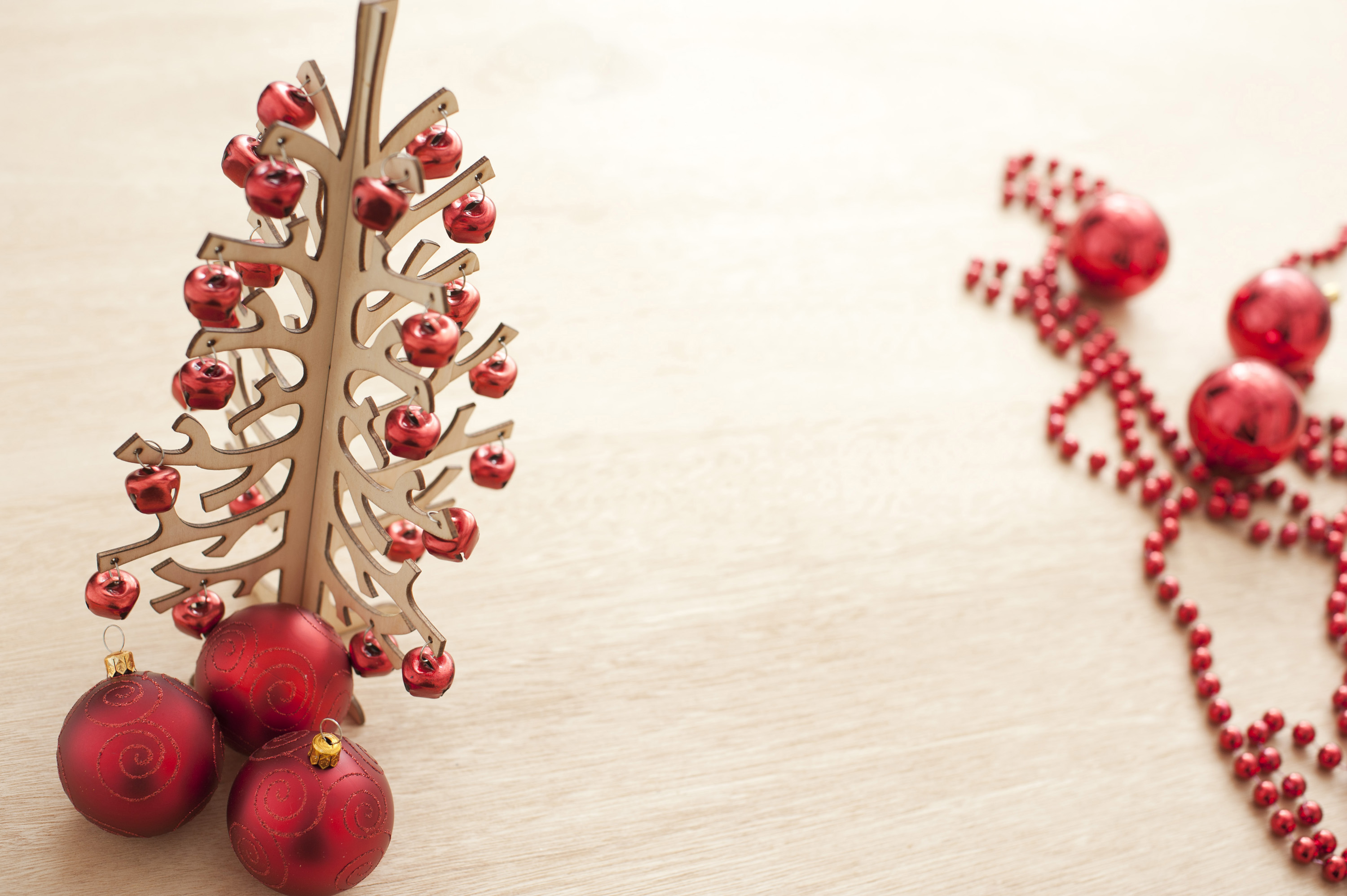 Wooden Christmas tree with red decorations on a modern table surface