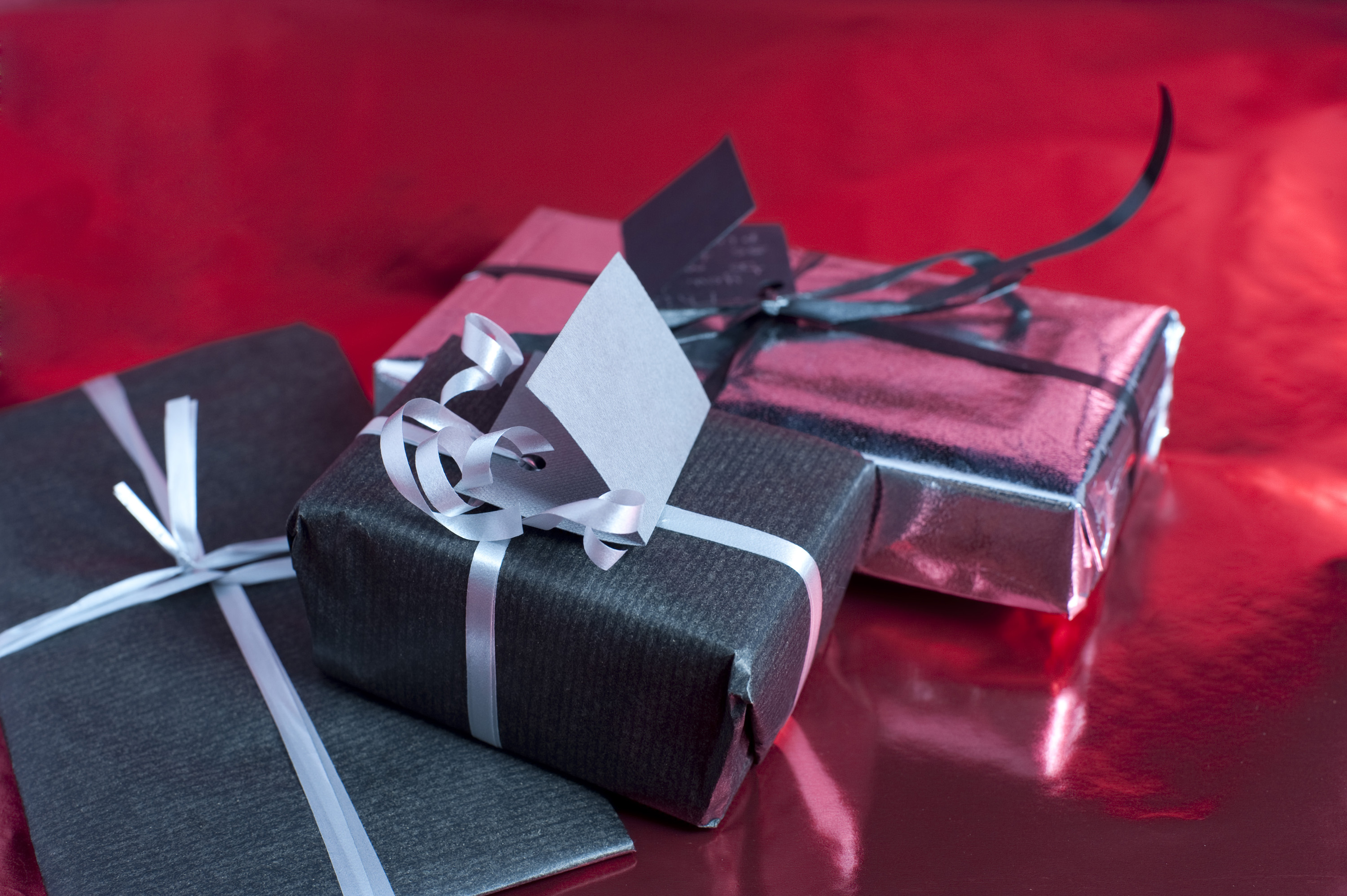 three small christmas presents wrapped with a bow of ribbon
