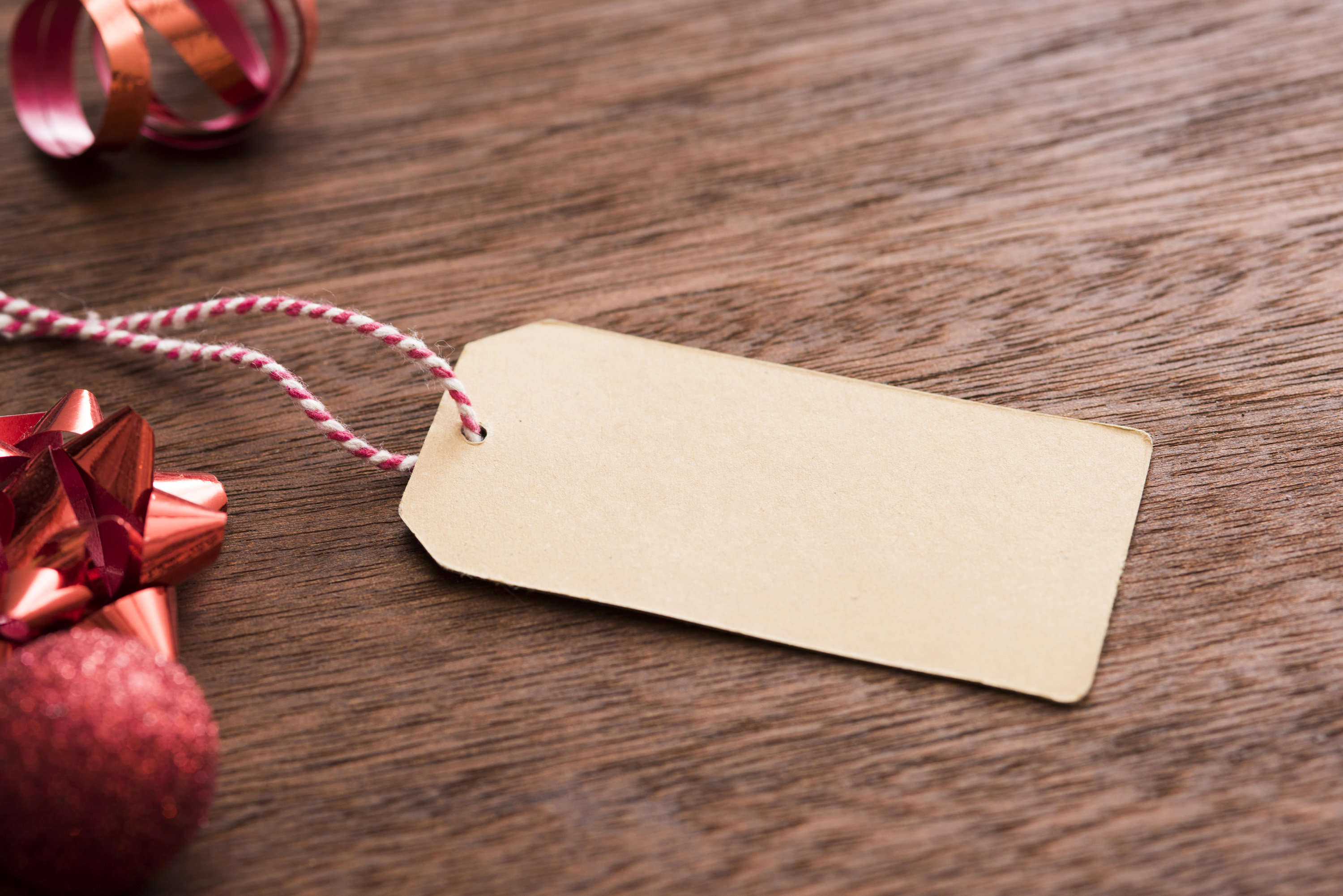Blank Christmas gift tag with red bow , baubles and ribbon forming a side border over textured wood, copy space for your holiday greeting