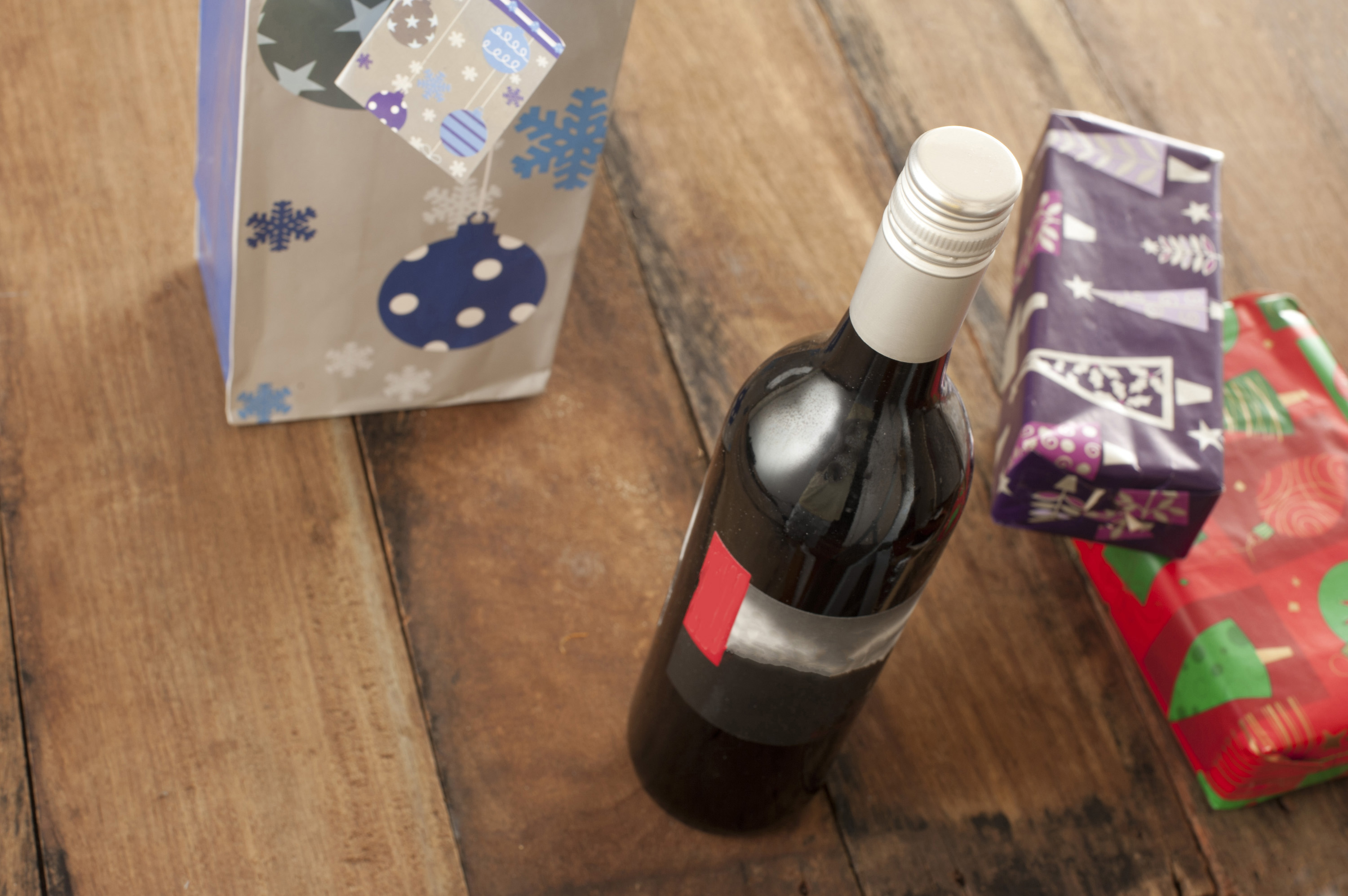 A bottle of wine standing beside some xmas presents on a wooden table