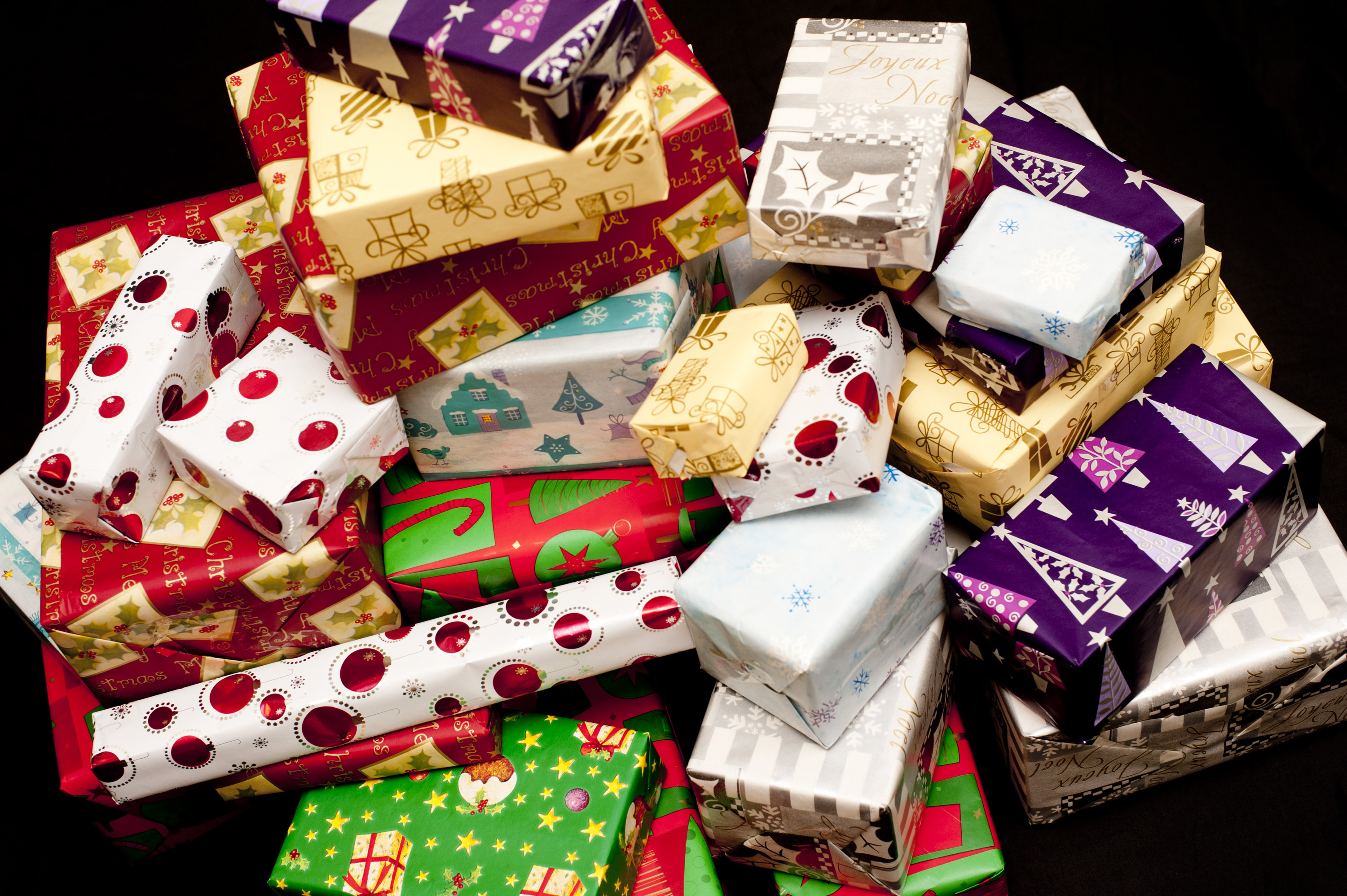 Pile of colorful gift wrapped Christmas gifts of assorted shapes and sizes in brightly colored patterned paper