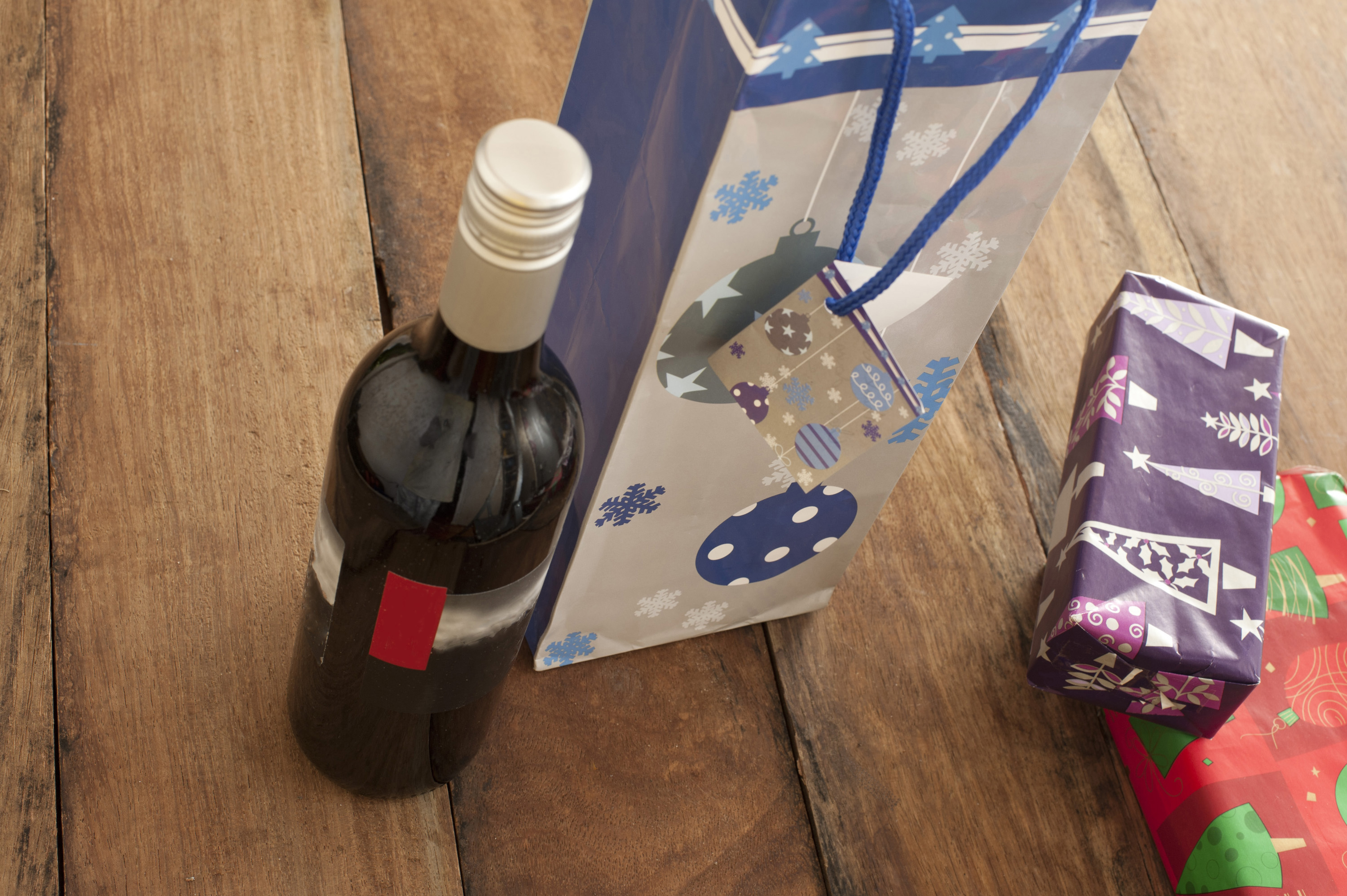 Bottle of red wine and Christmas presents on wooden table