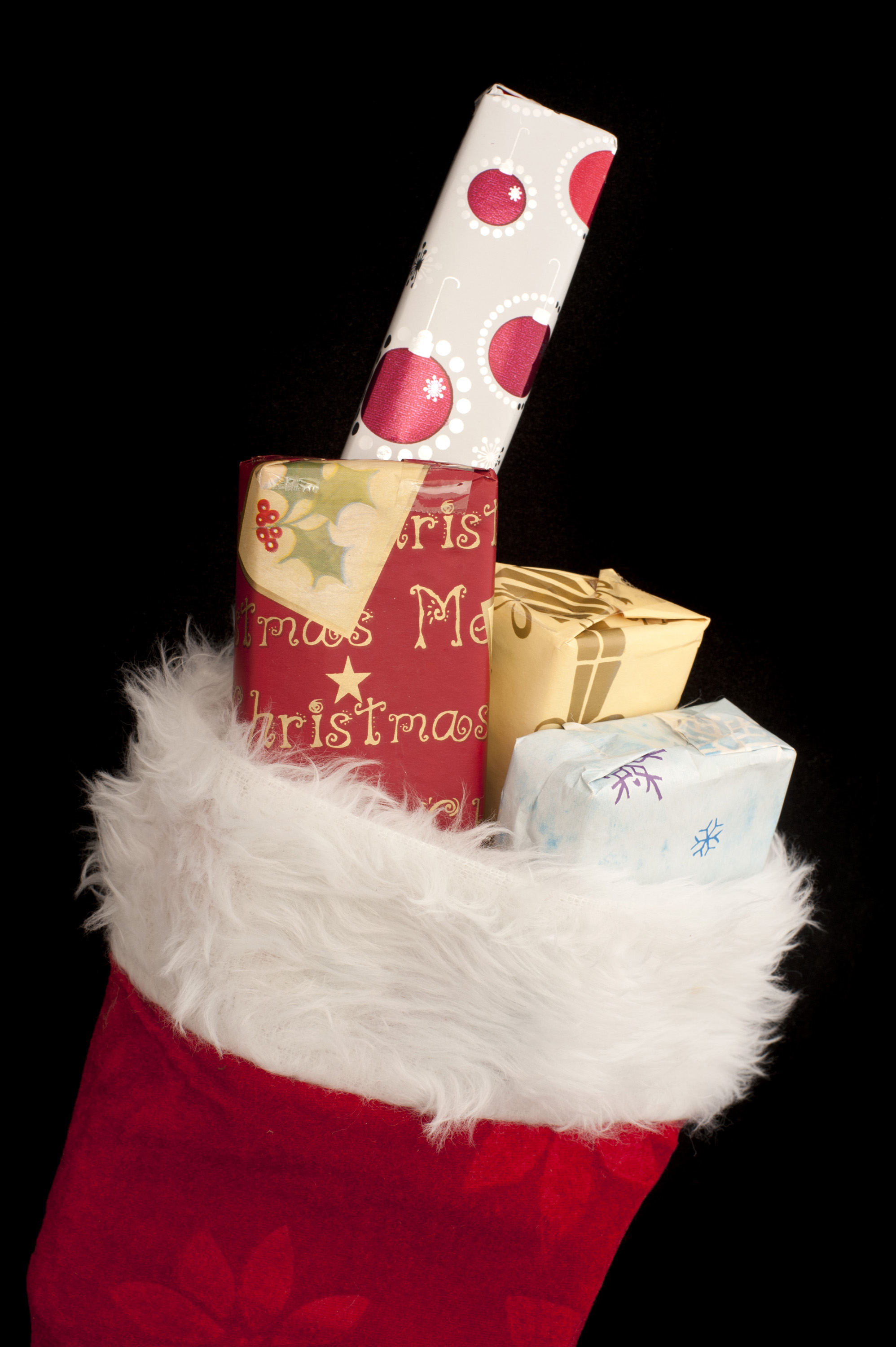Festive red Christmas stocking filled with red , white and gold themed gifts over a black background