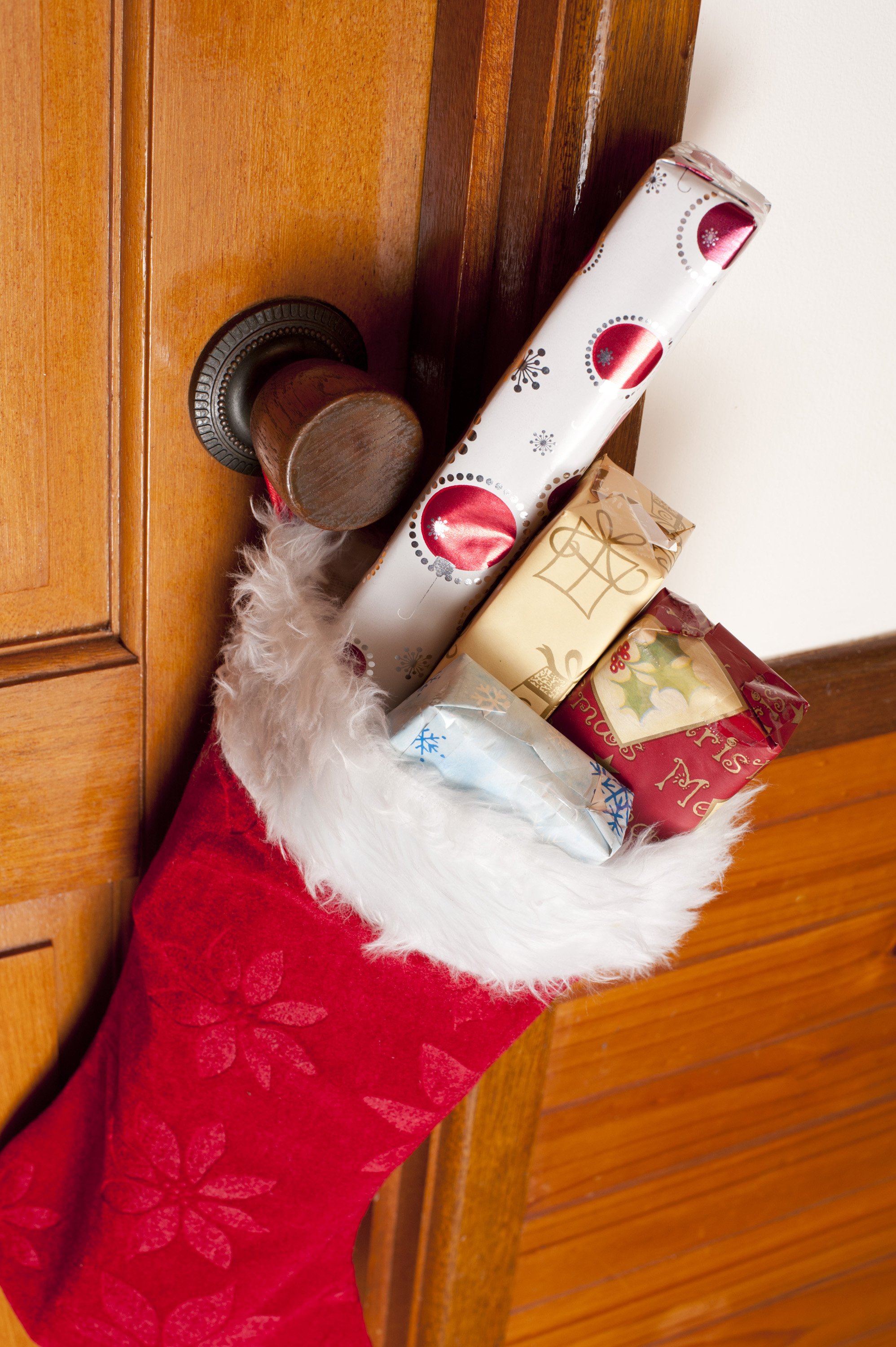 Colorful Christmas gifts filling a red stocking hanging from a wooden door in a close up view with copy space