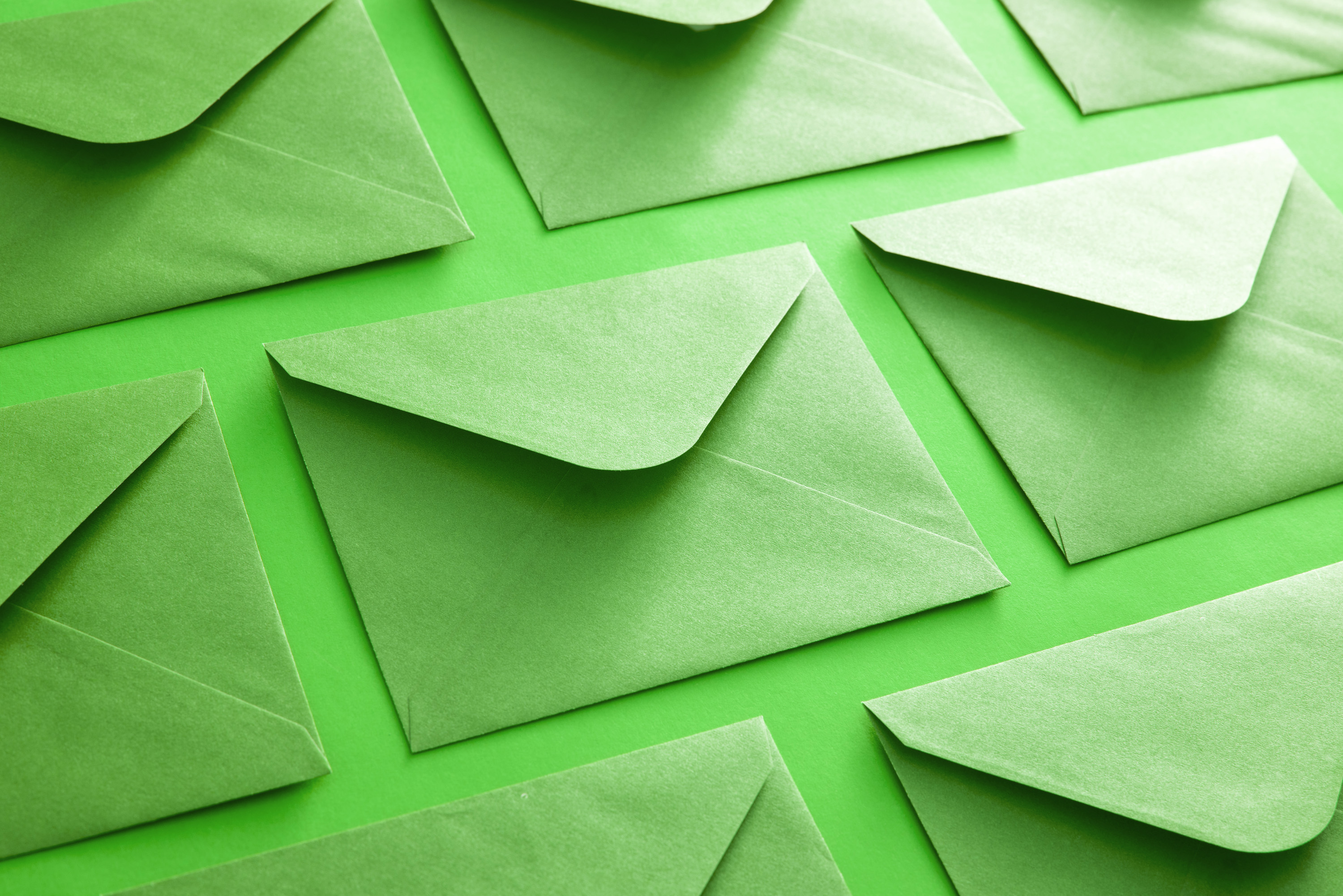 Colorful green envelope background neatly arranged face down with open flaps in diagonal rows in a correspondence and communication concept