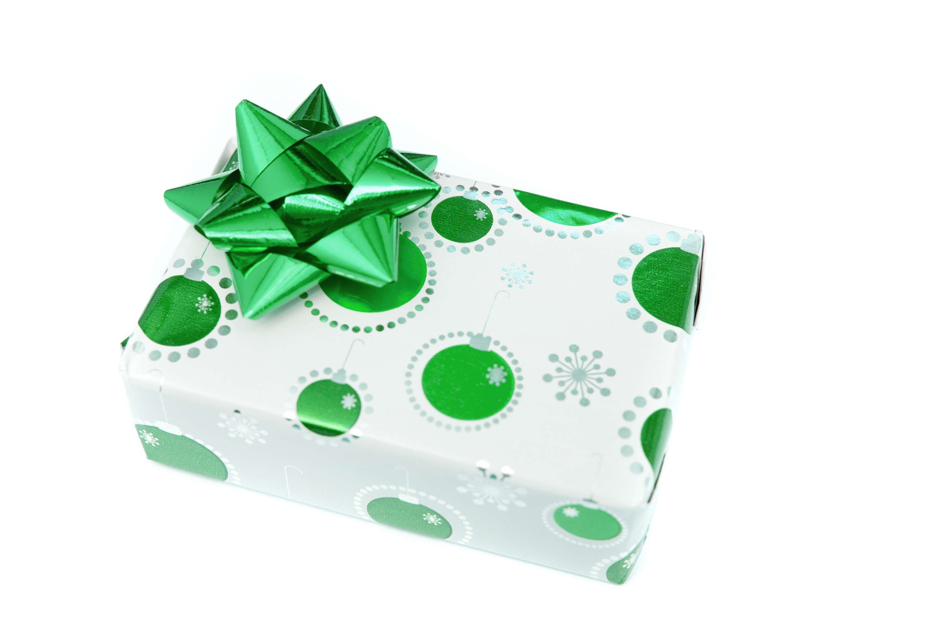Decorative green Christmas gift box with bow and patterned seasonal paper with Xmas baubles isolated on white