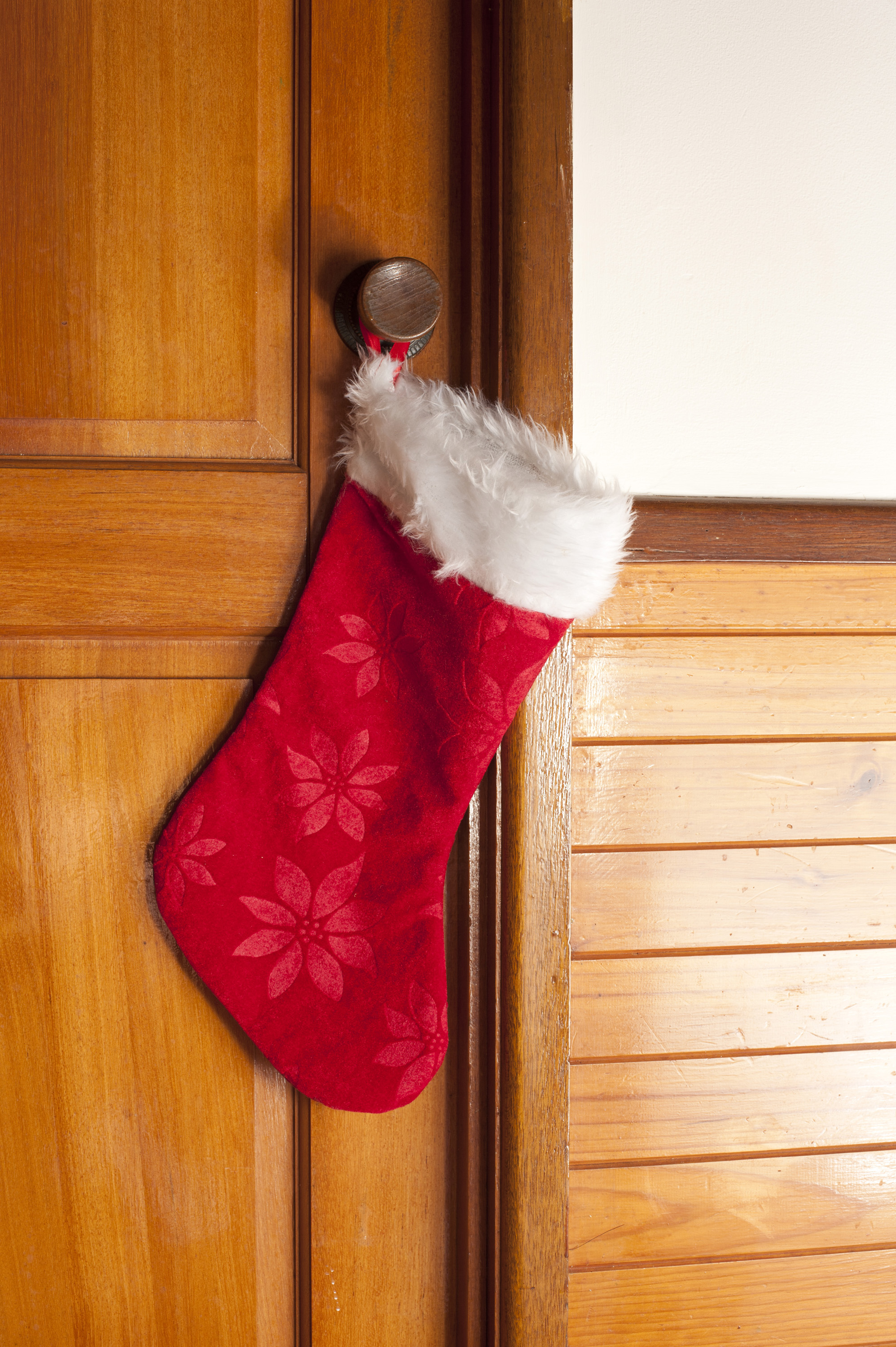 Empty decorative red Christmas stocking hanging on the handle of a wooden door waiting to be filled with gifts on Xmas Eve