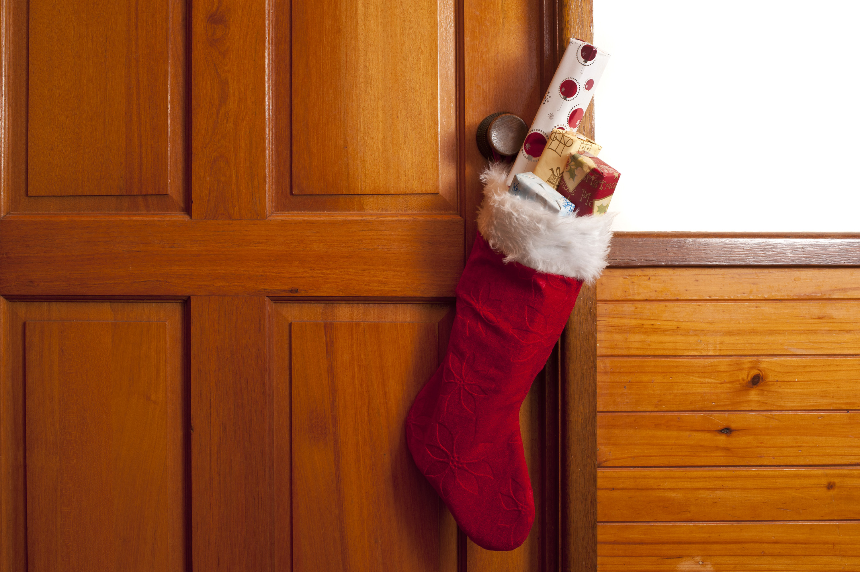 Full festive red Christmas stocking filled with tiny gifts hanging on a wooden door with copy space over a white interior panel