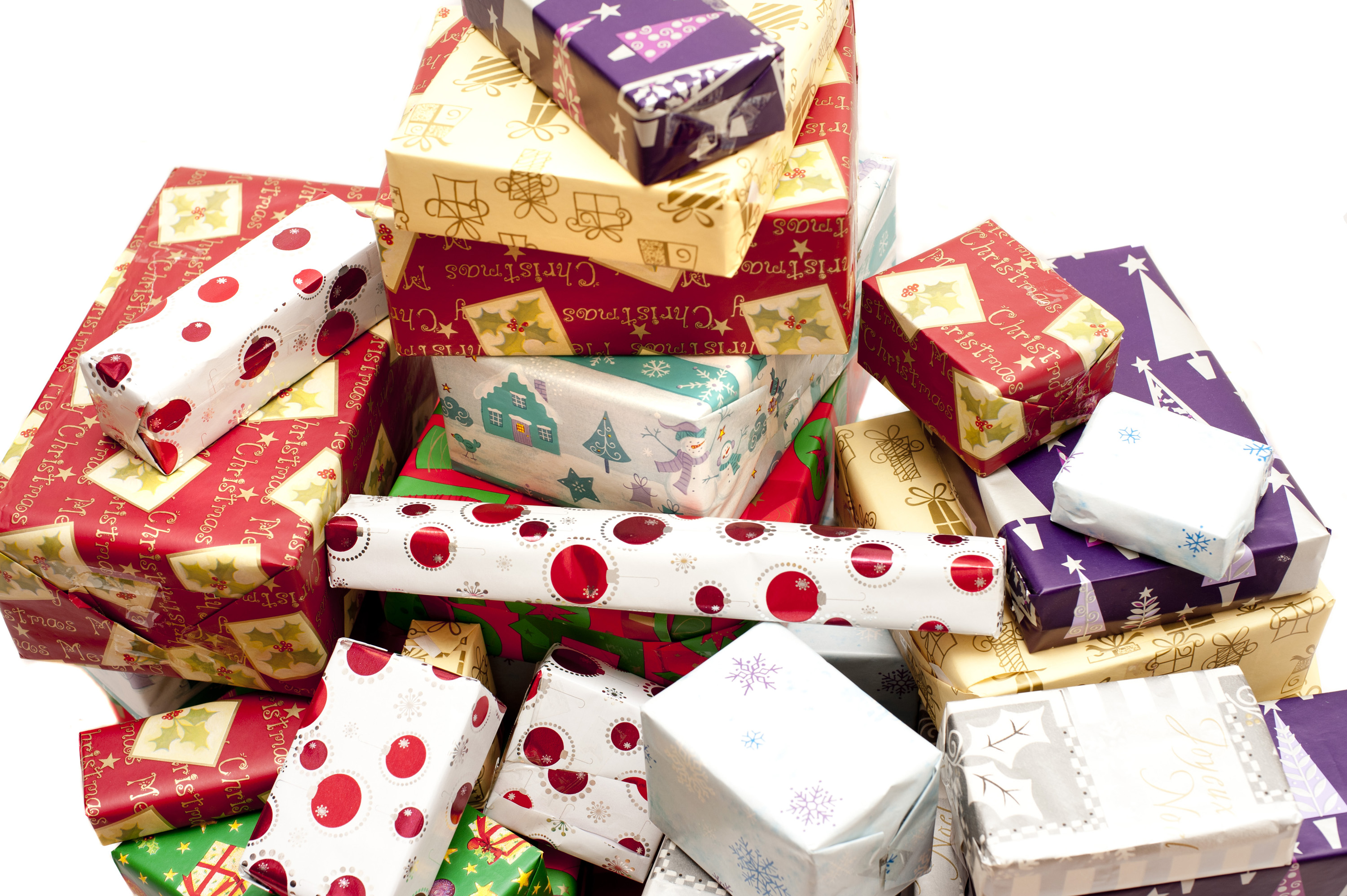 Large pile of multicolored Christmas gifts in decorative seasonal wrapping paper in a close up background view over white