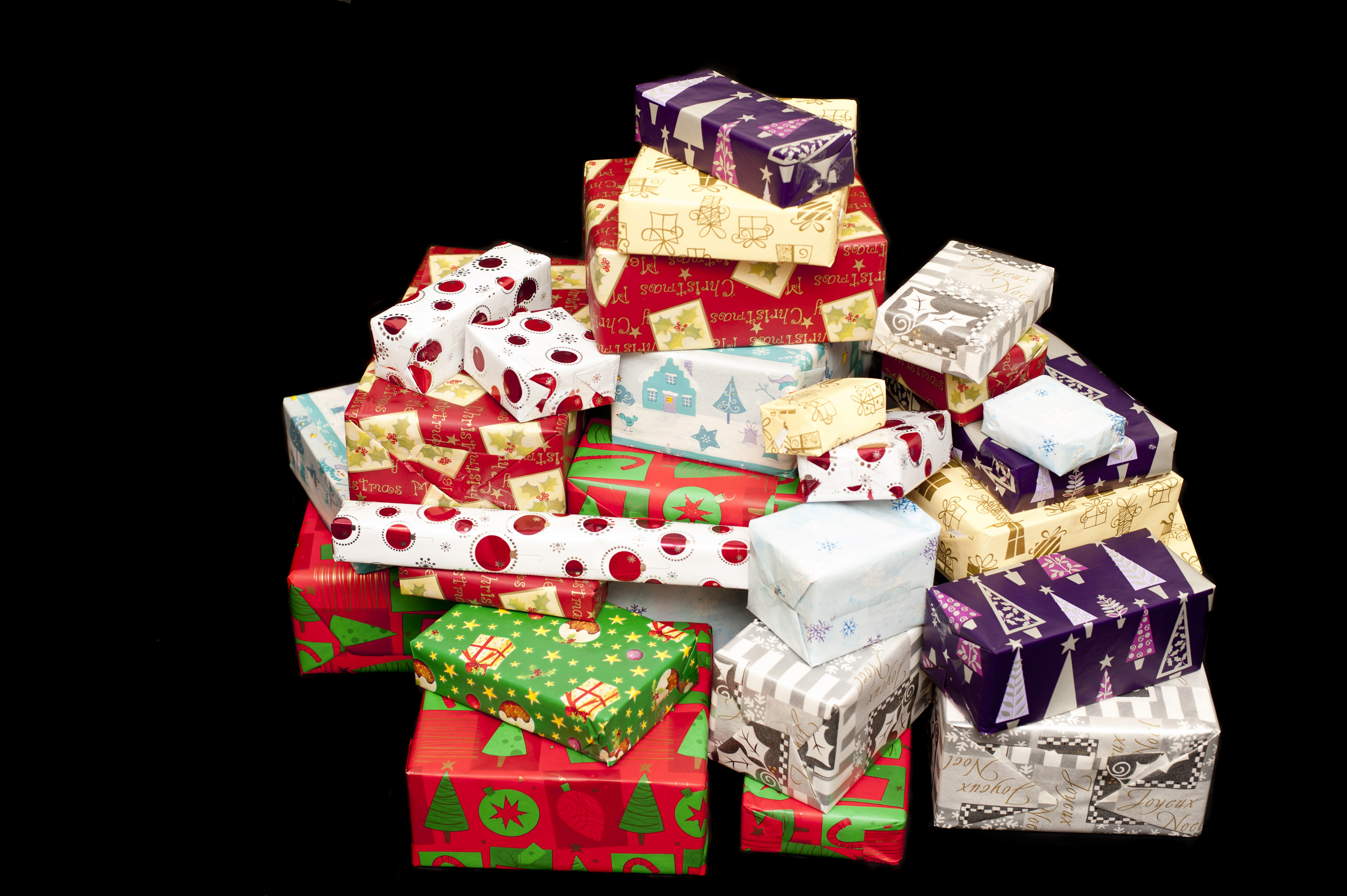 Pile of colorful Christmas gifts in assorted seasonal patterned wrapping paper on black with copy space
