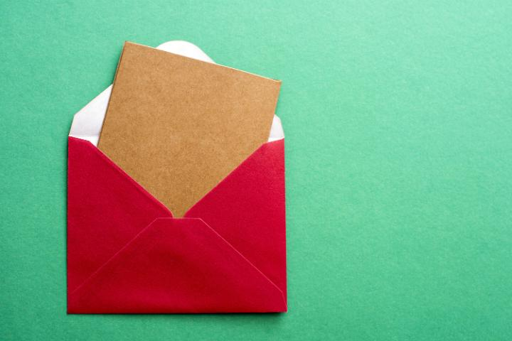 photo of blank christmas card in a festive red envelope