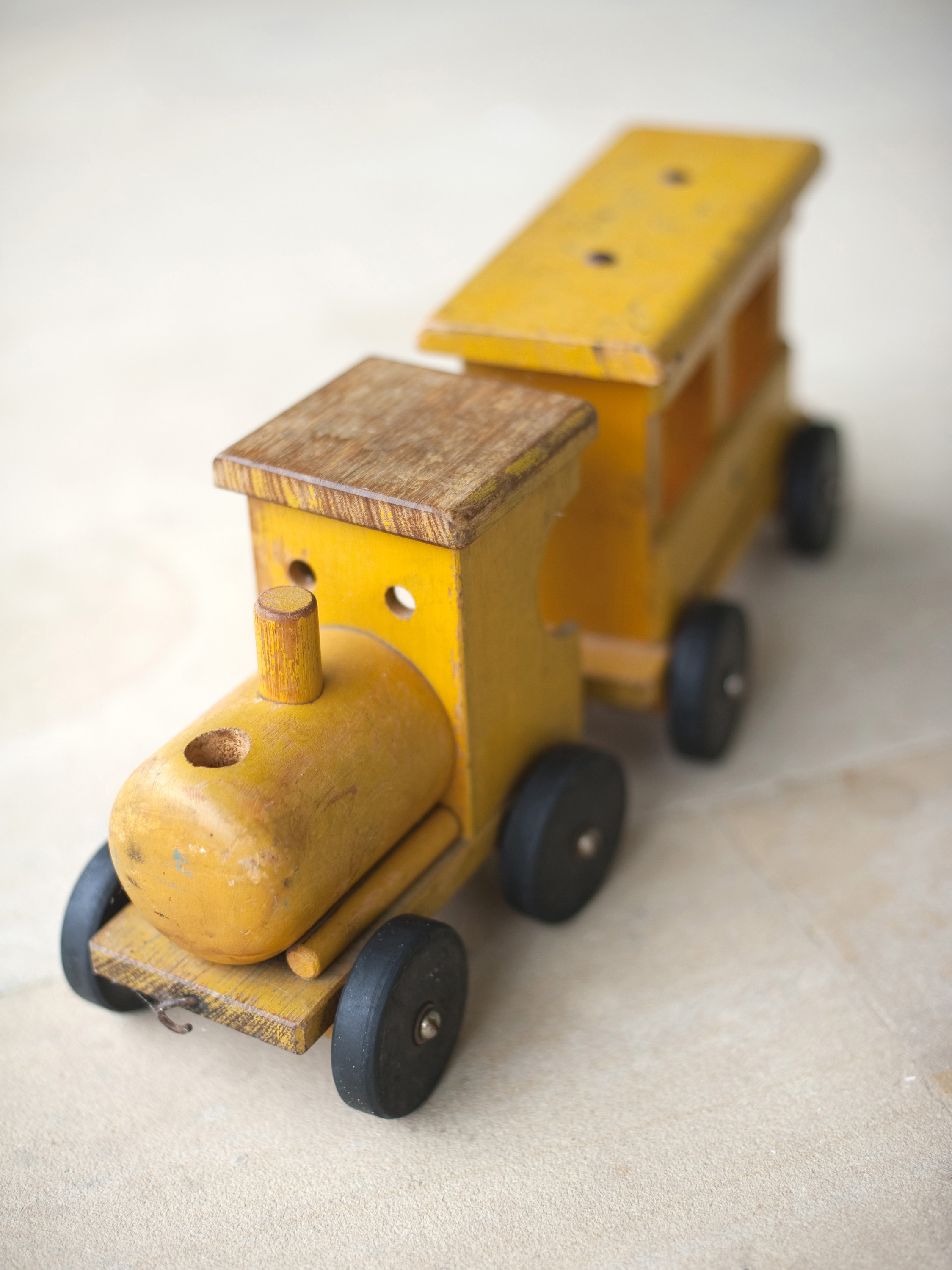 Close up shot of toy wooden train in yellow color being on white surface.