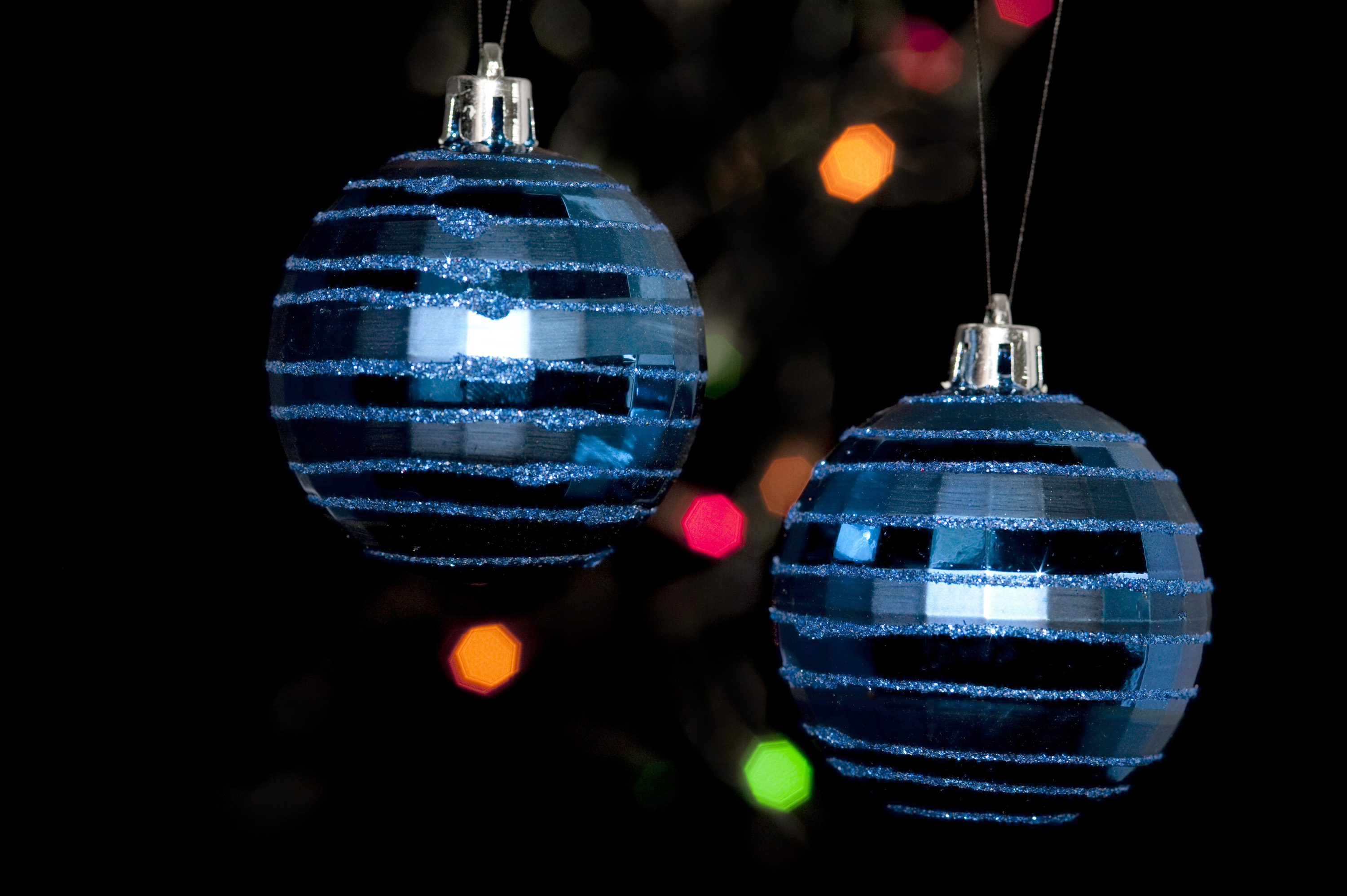 two christmas tree balls hanging on a dark backdrop of frestive colourful lights in the rear