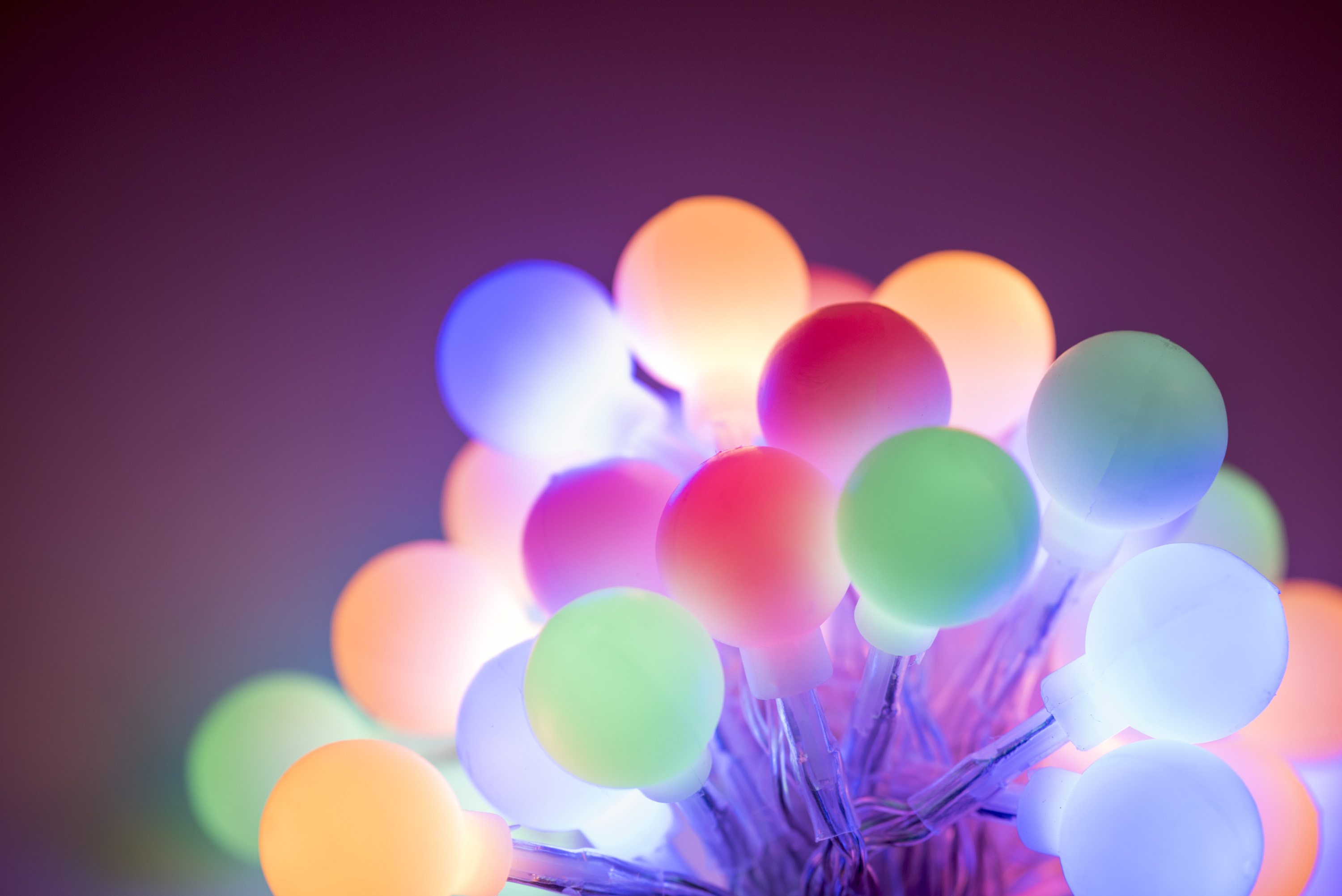 Glowing cluster of round Christmas berry lights in assorted muted hues shining in the darkness for a festive holiday background