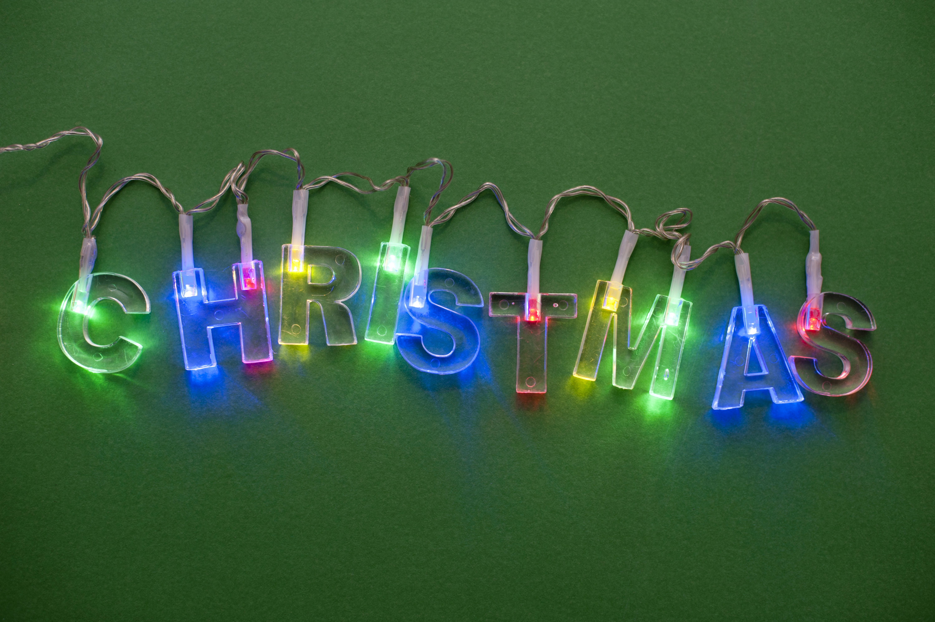 Christmas garland spelling out christmas in coloured light on green background