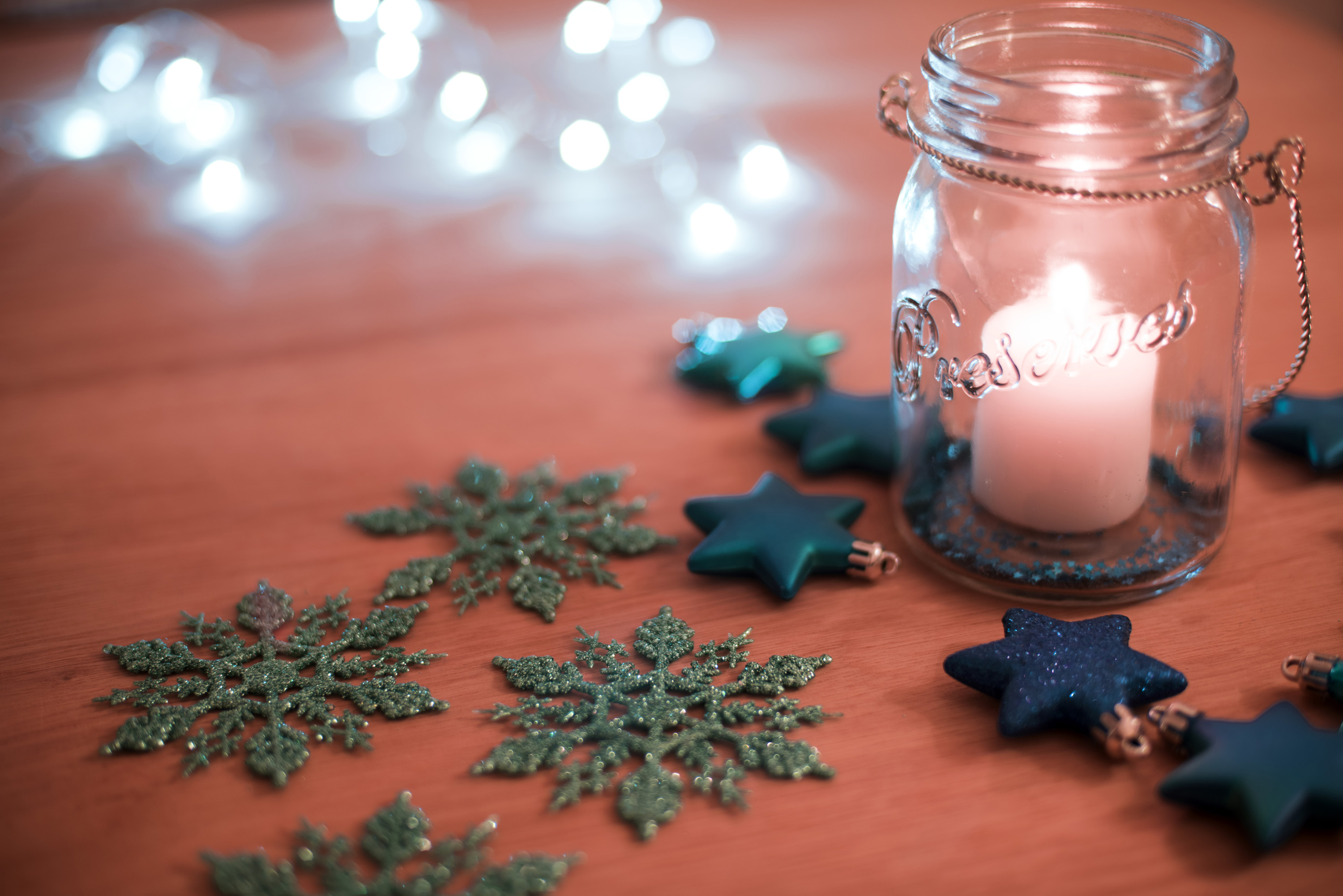 Burning Christmas candle in a glass jar casting a soft glow over surrounding snowflake and star decorations with a party light bokeh background