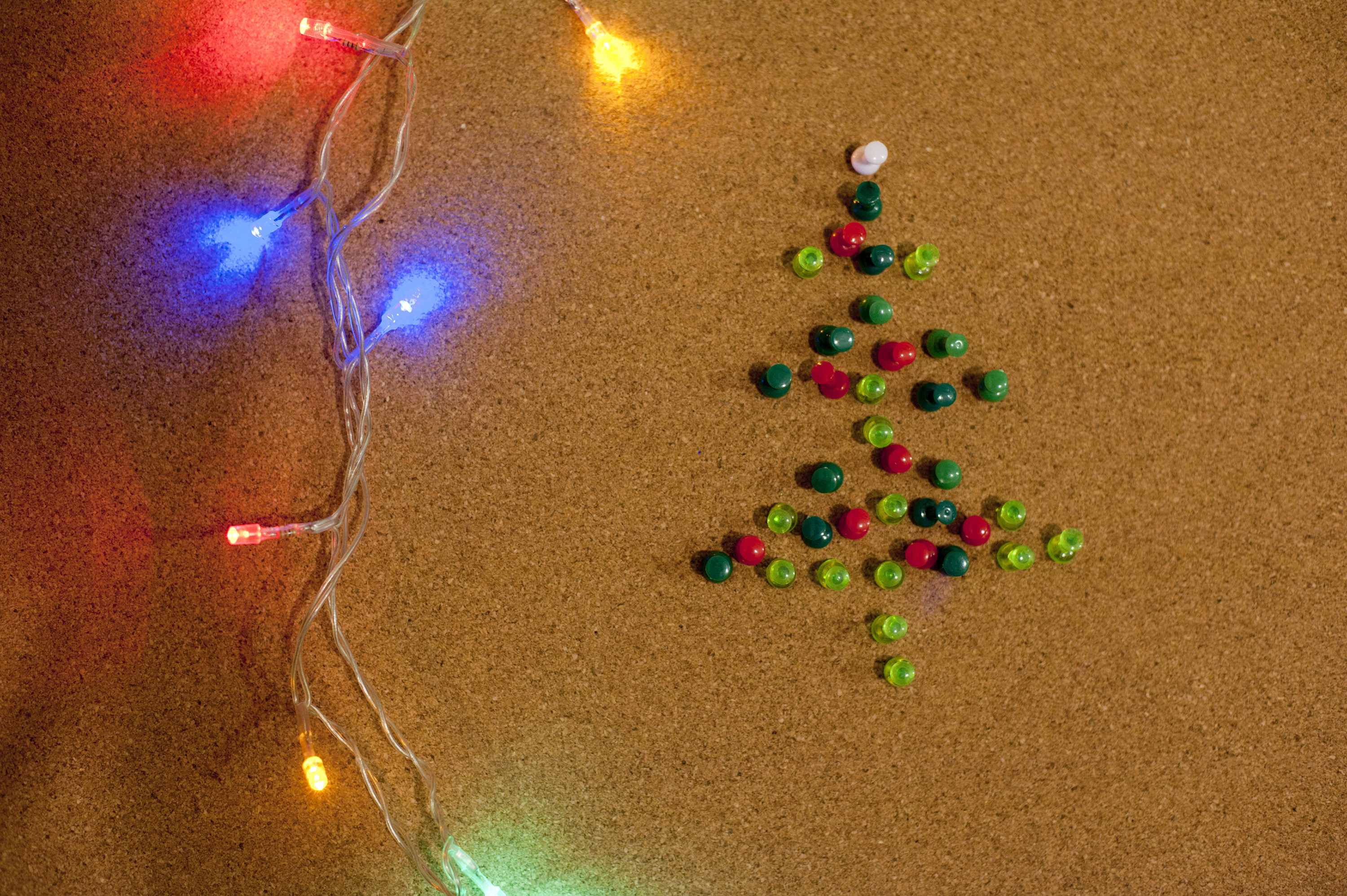 Close-up of lighted garland and handmade Christmas tree made of colorful pins. From above