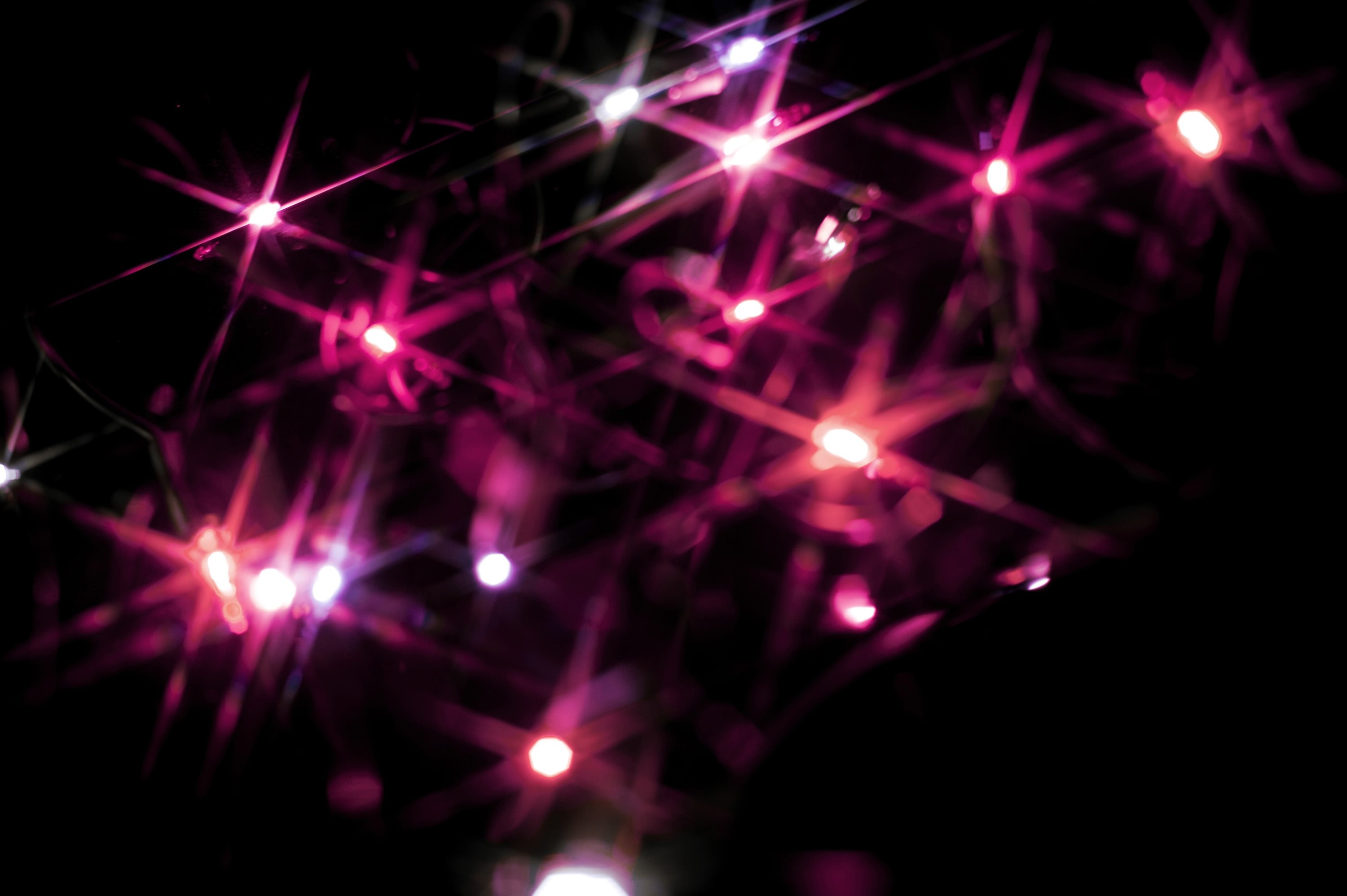 Christmas background of colourful vivid pink starburst lights scattered in the darkness sparkling and glowing for a fesive greeting card or seasonal wishes