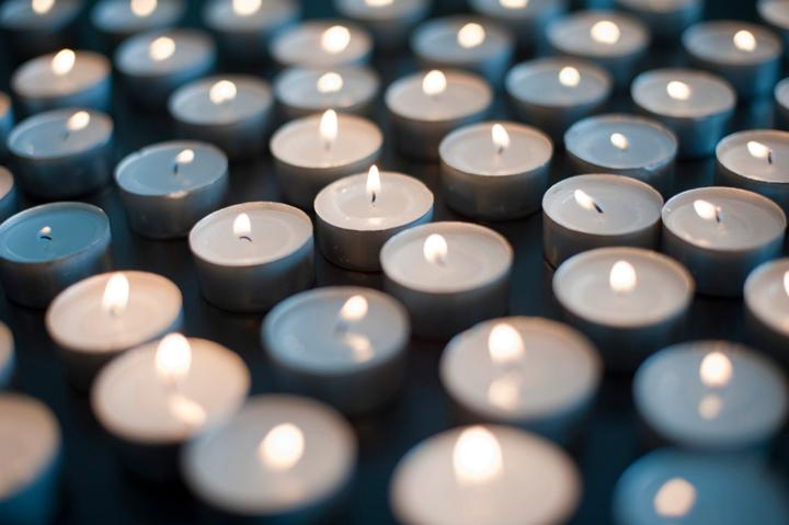 narrow depth of field image of many lit christmas candles