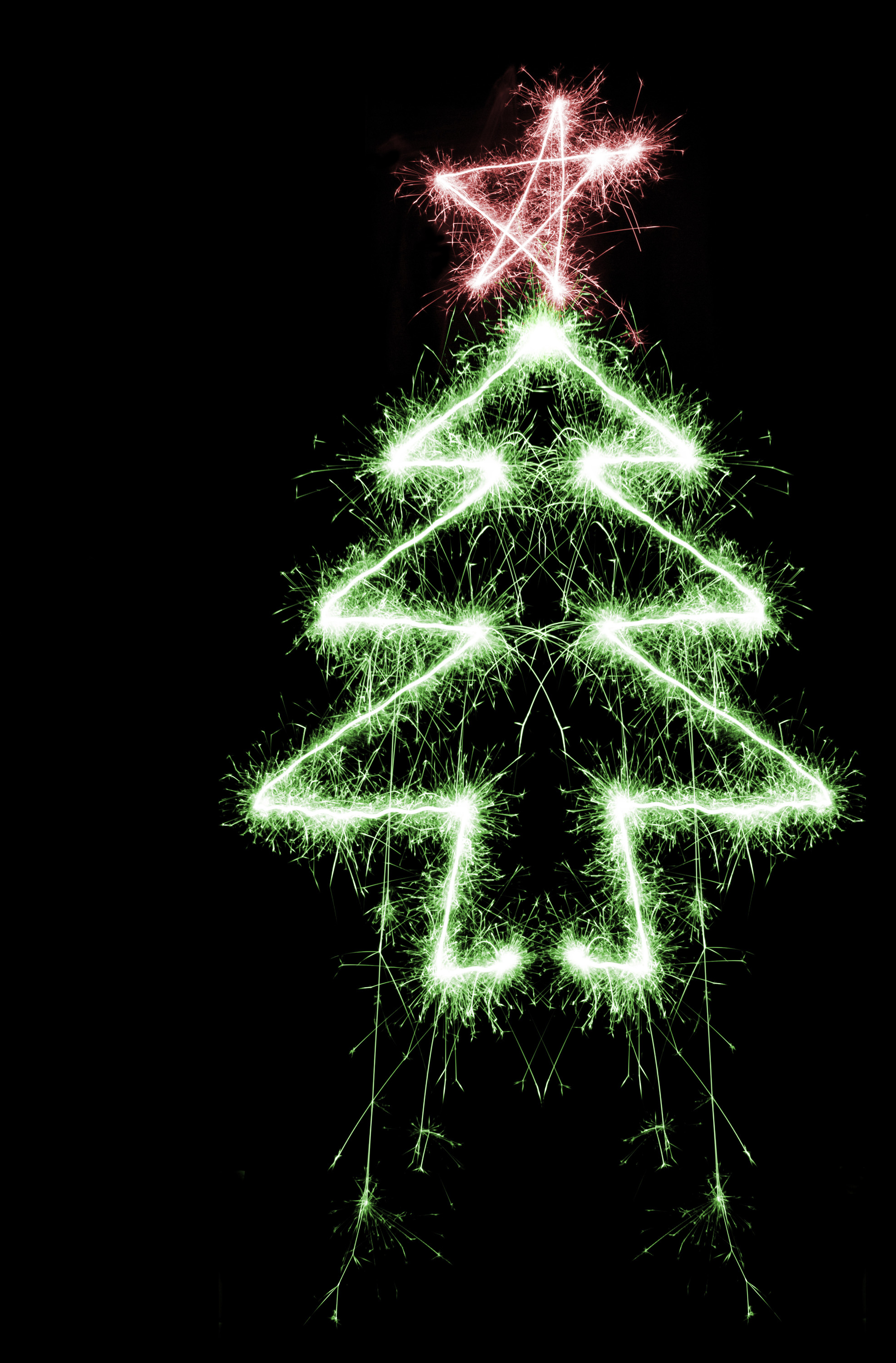 a green and red coloured christmas tree and star shape drawn with a sparkler