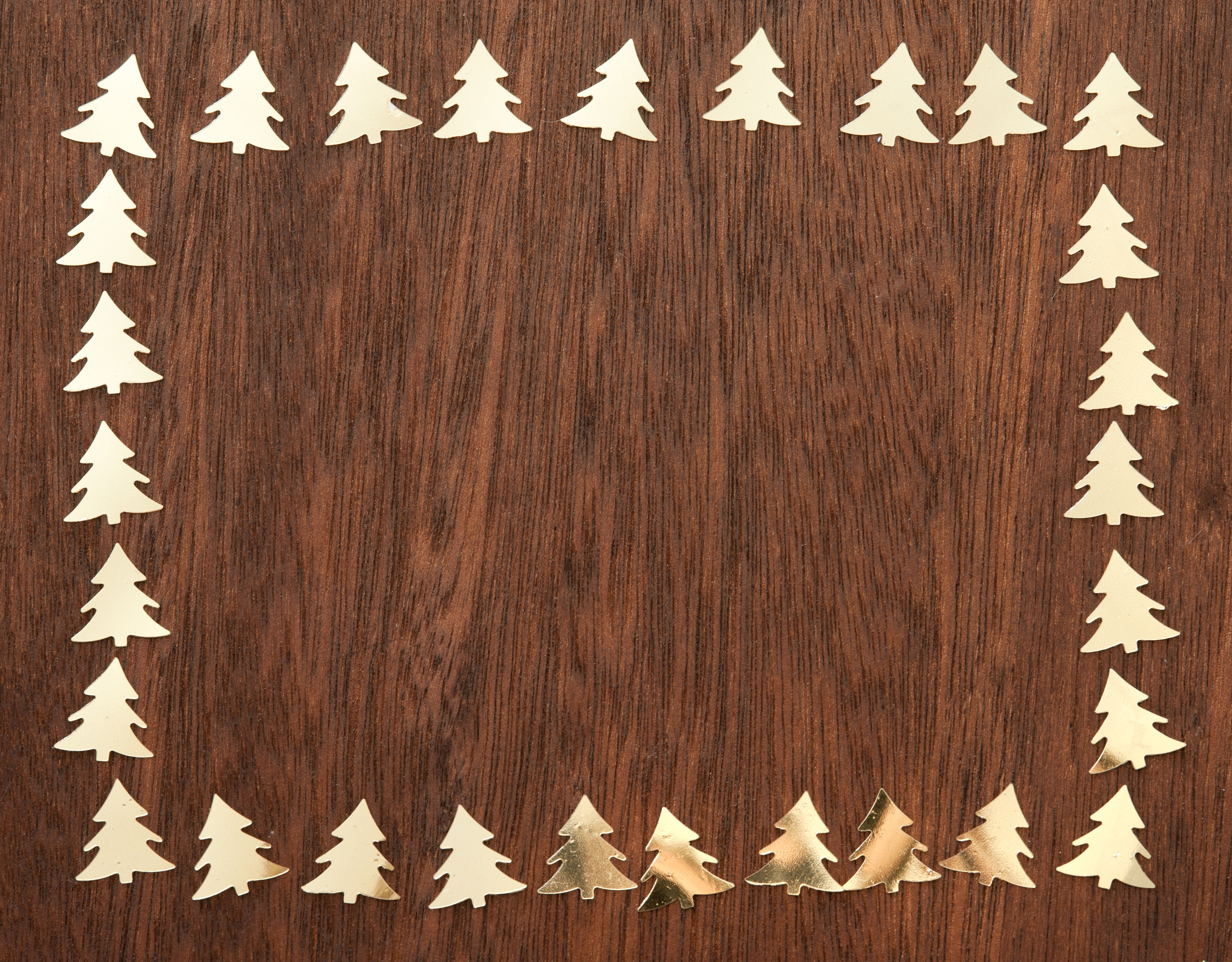 Several Cut Golden Fir Trees Around Edges On Wooden Table From Above
