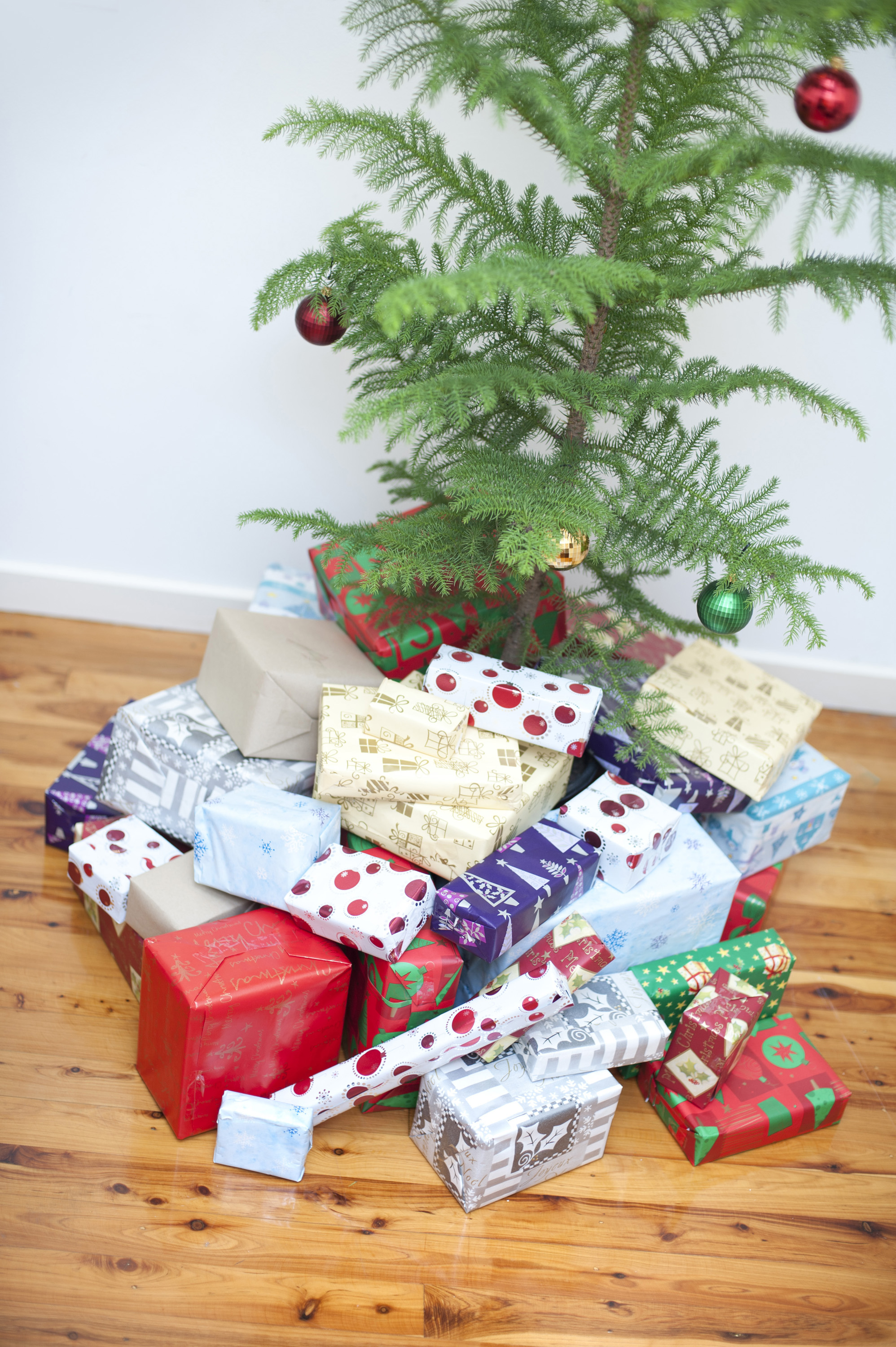 pile of colourful gift wrapped christmas gifts in an assortment of pretty patterned paper lying