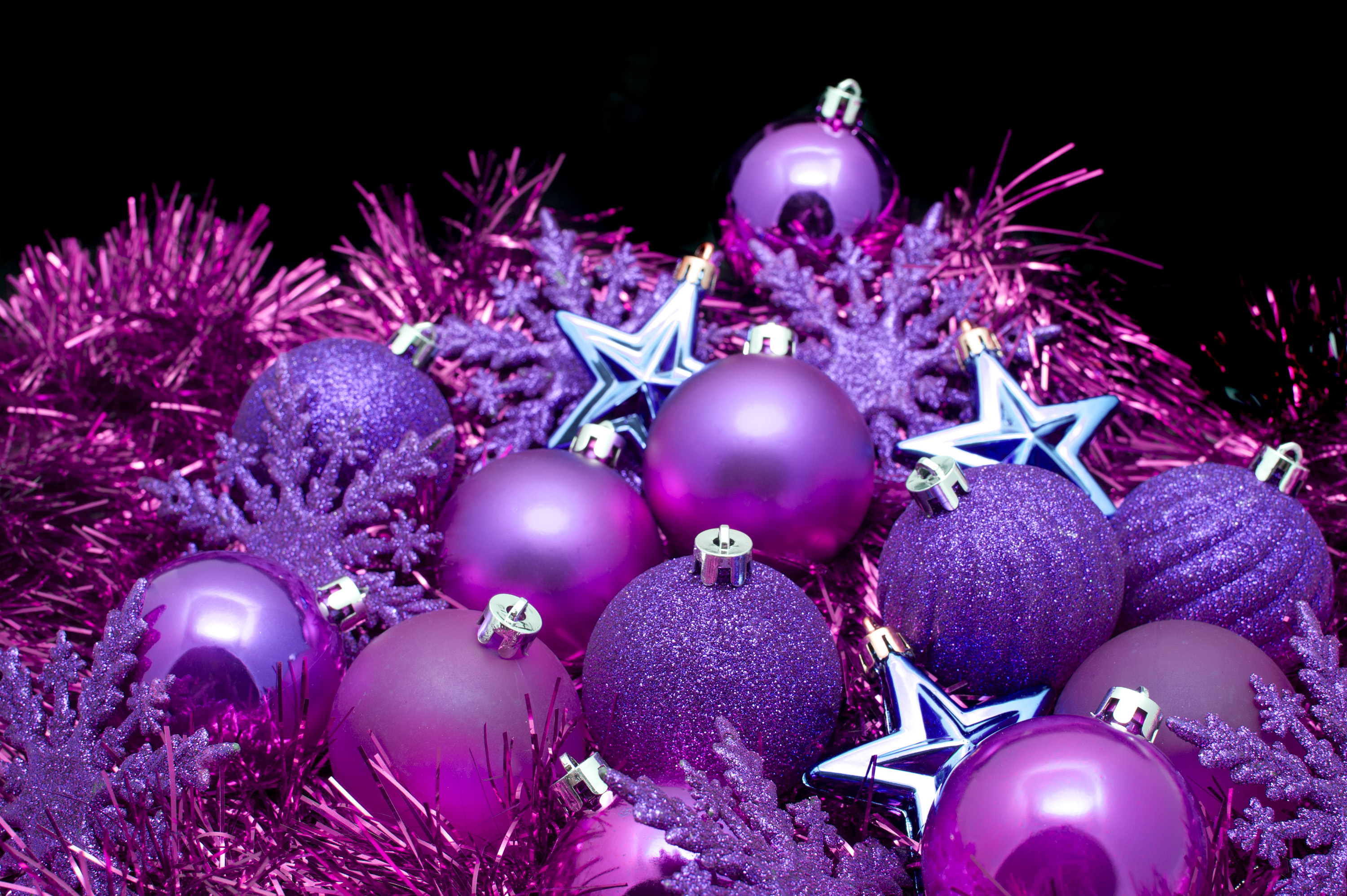 background arrangement of purple christmas decorations with tinsel stars baubles and snowflakes