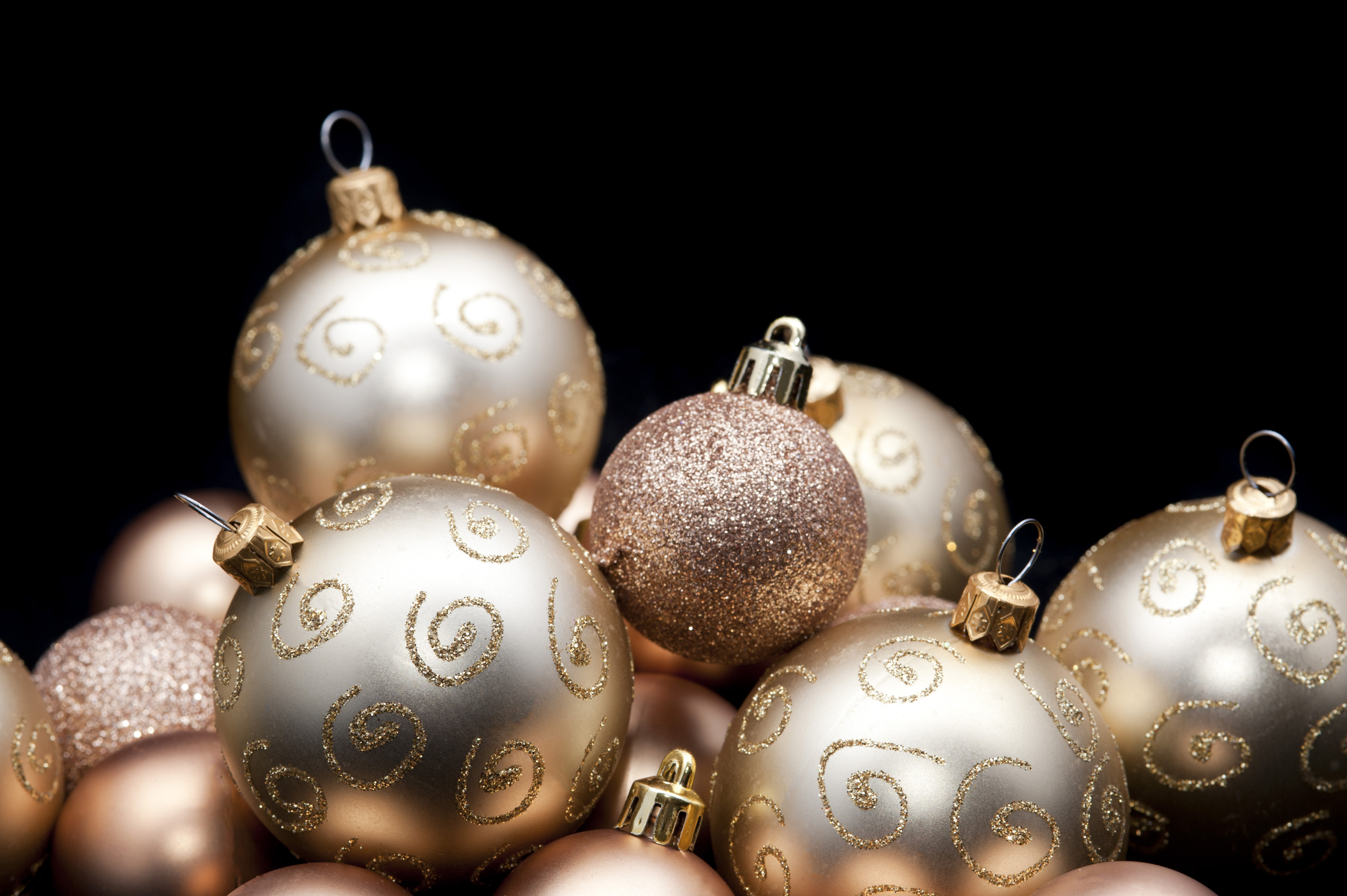 a black background with copyspace framed with a selection of glittery gold christmas ornaments