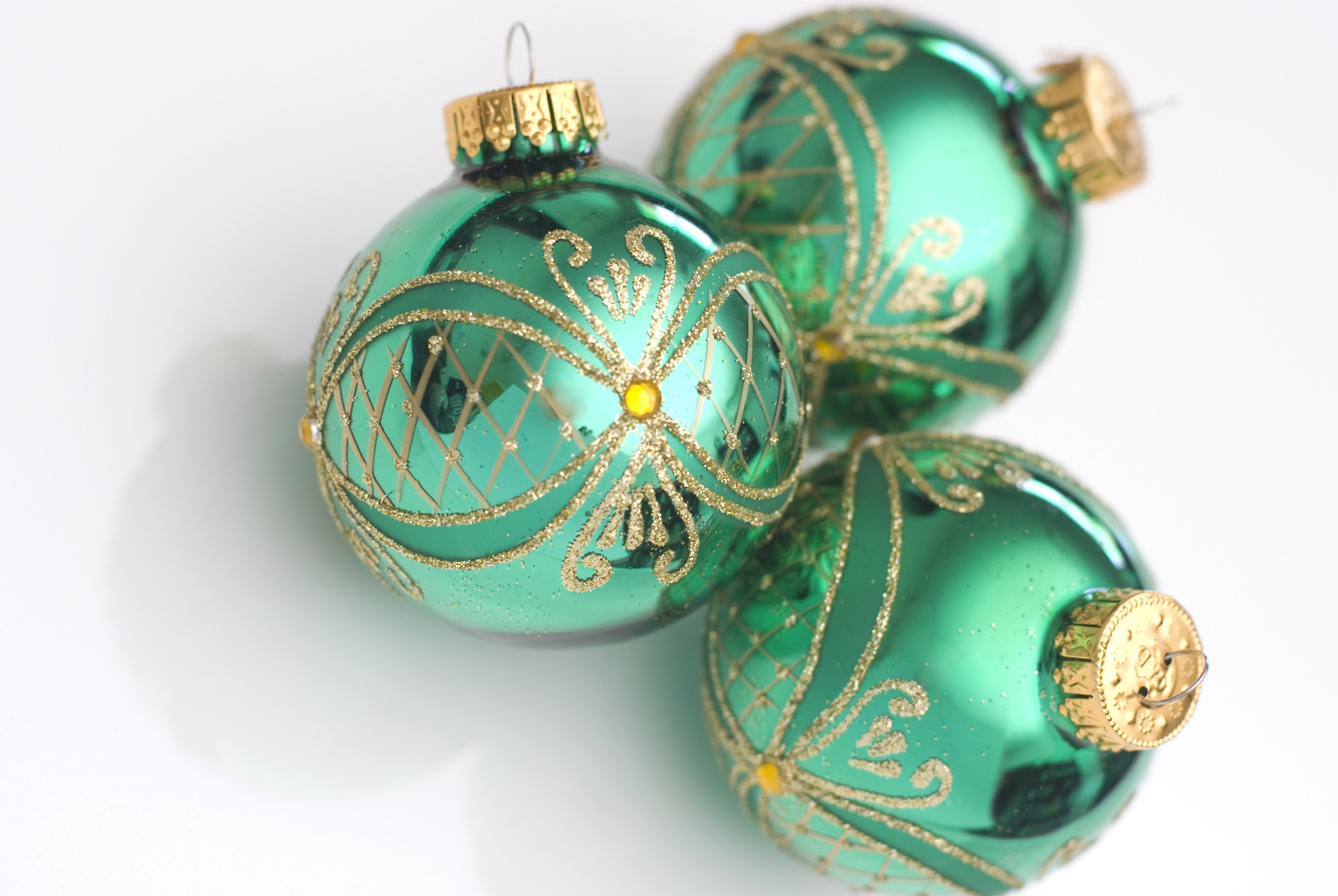 three green glass christmas ornaments on a plain white background narrow depth of field image