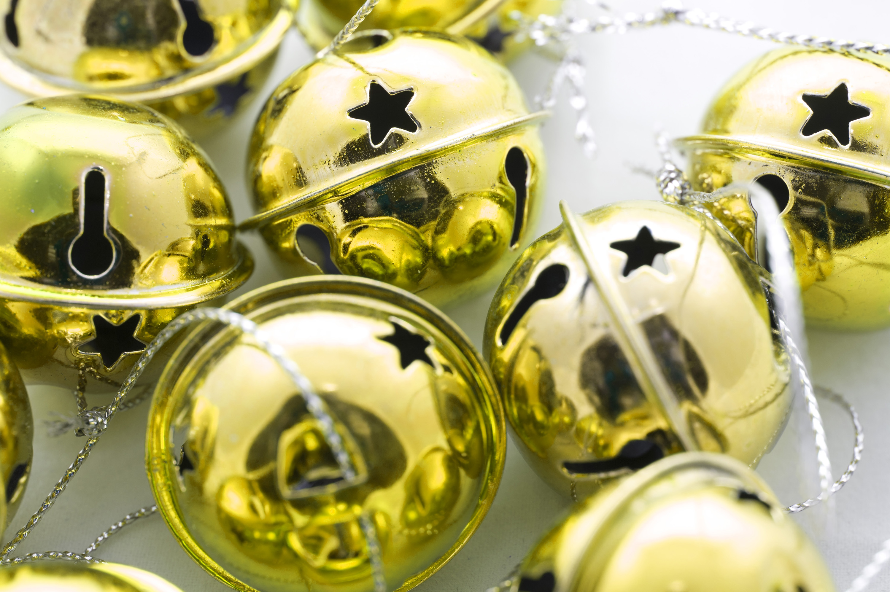 closeup of shiny gold metallic round christmas jingle bell ornaments with ties to hang on your