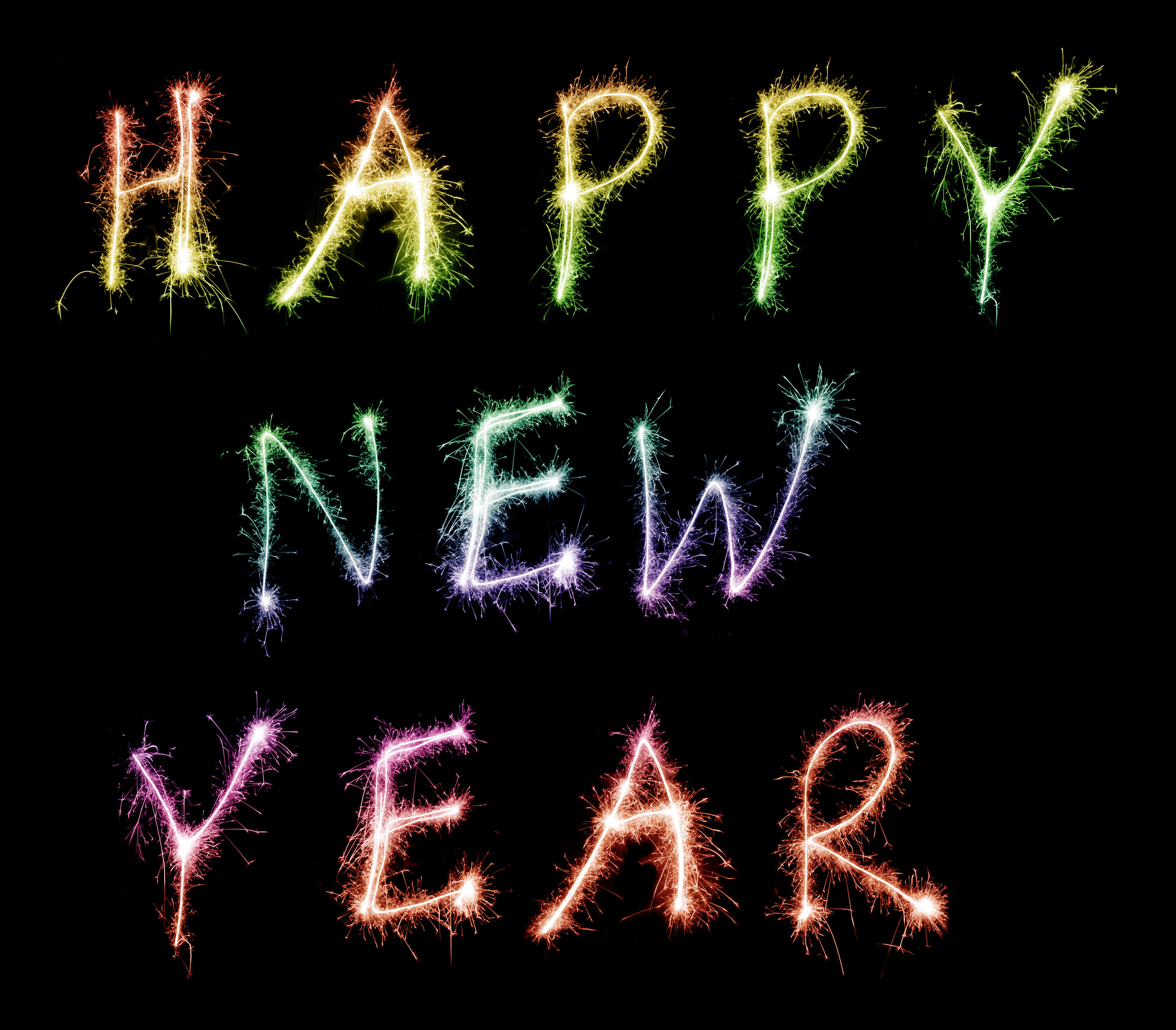happy new year written in colourful multicoloured sparklers on a black background for your greetings and