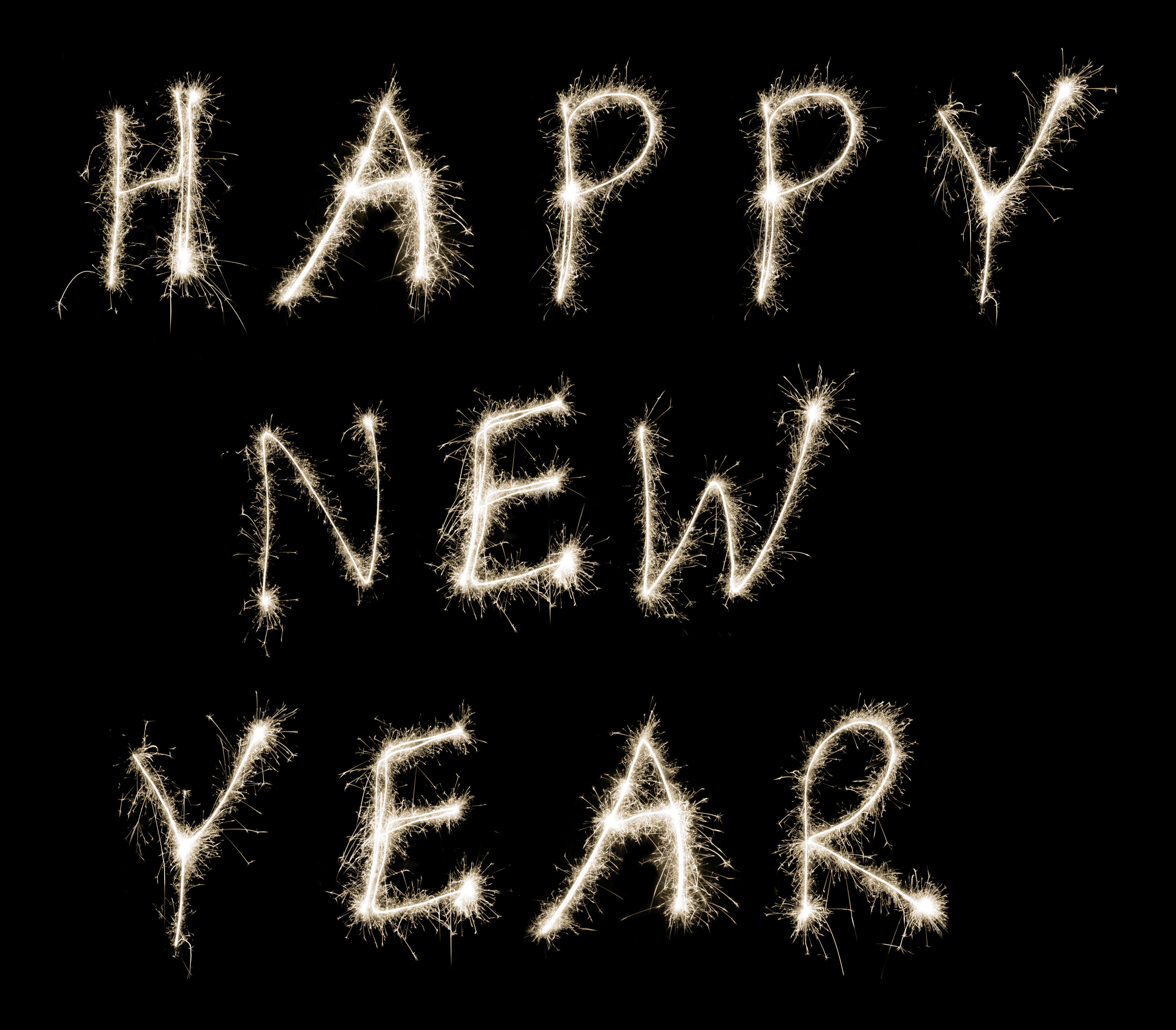happy new year text written in fiery white sparklers on a black background to welcome in