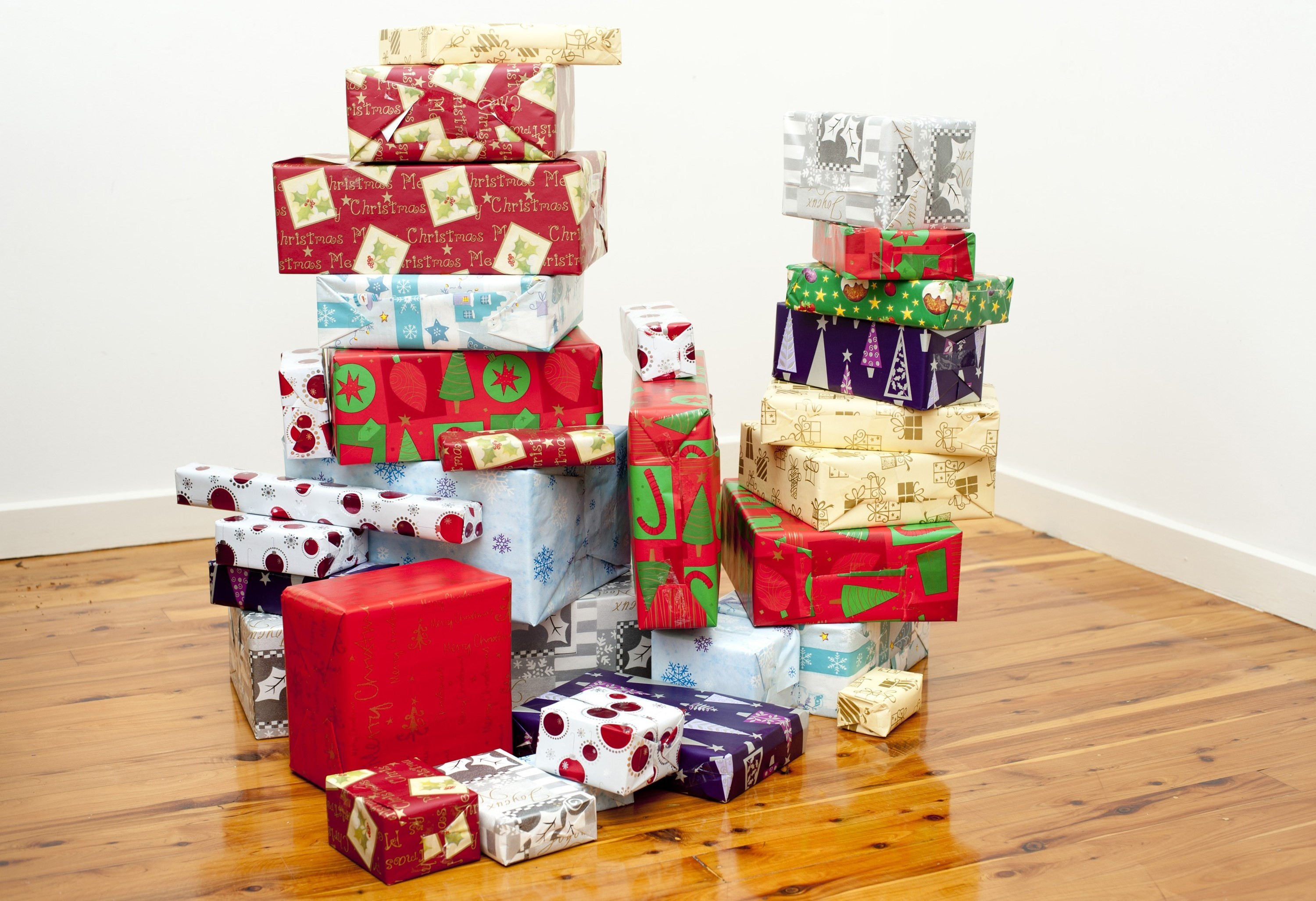 pile of gift boxes wrapped in decorative wrapping paper with seasonal patterns indoors