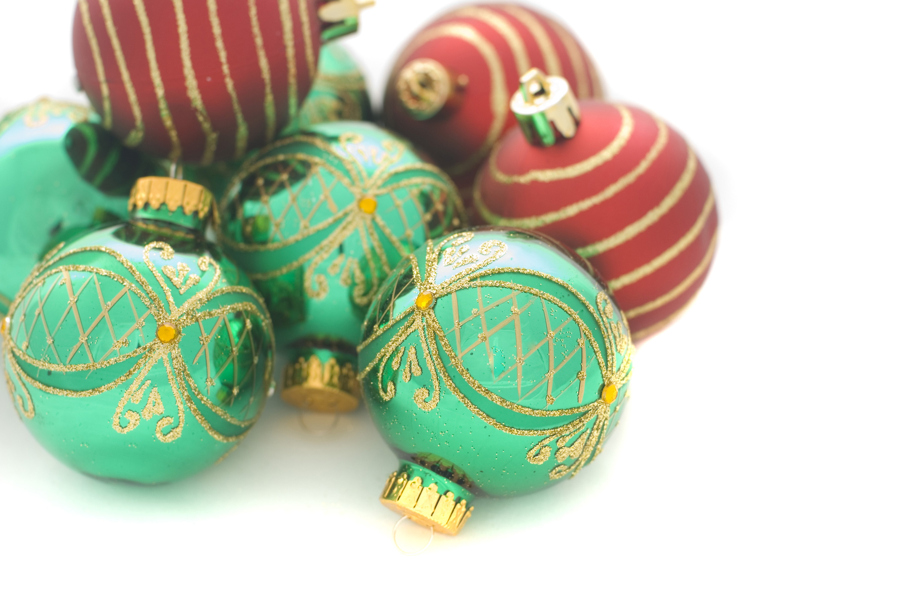 A Pile Of Red And Green Christmas Tree Ornaments On A Clean White Background