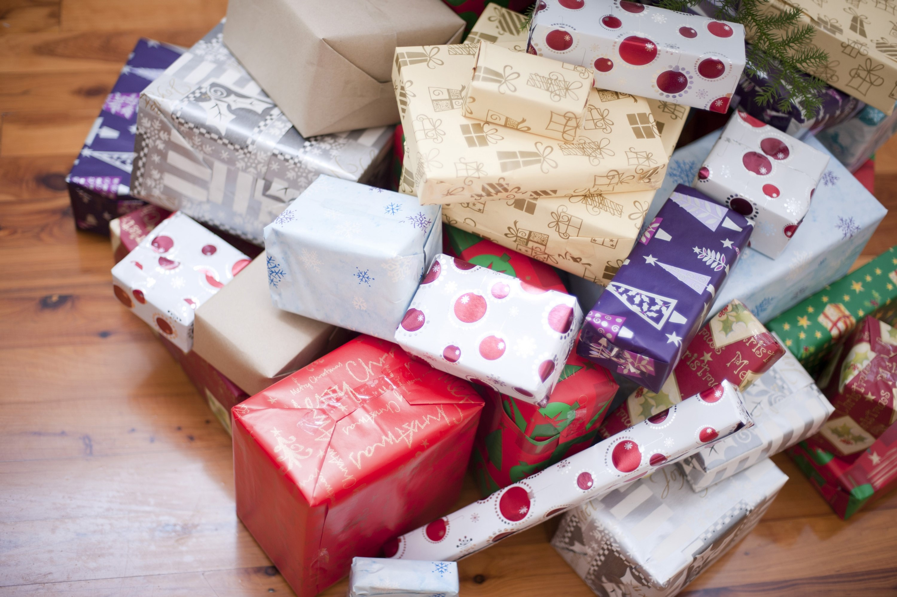 pile of gift wrapped christmas presents and gifts in an assortment of colourful patterned paper