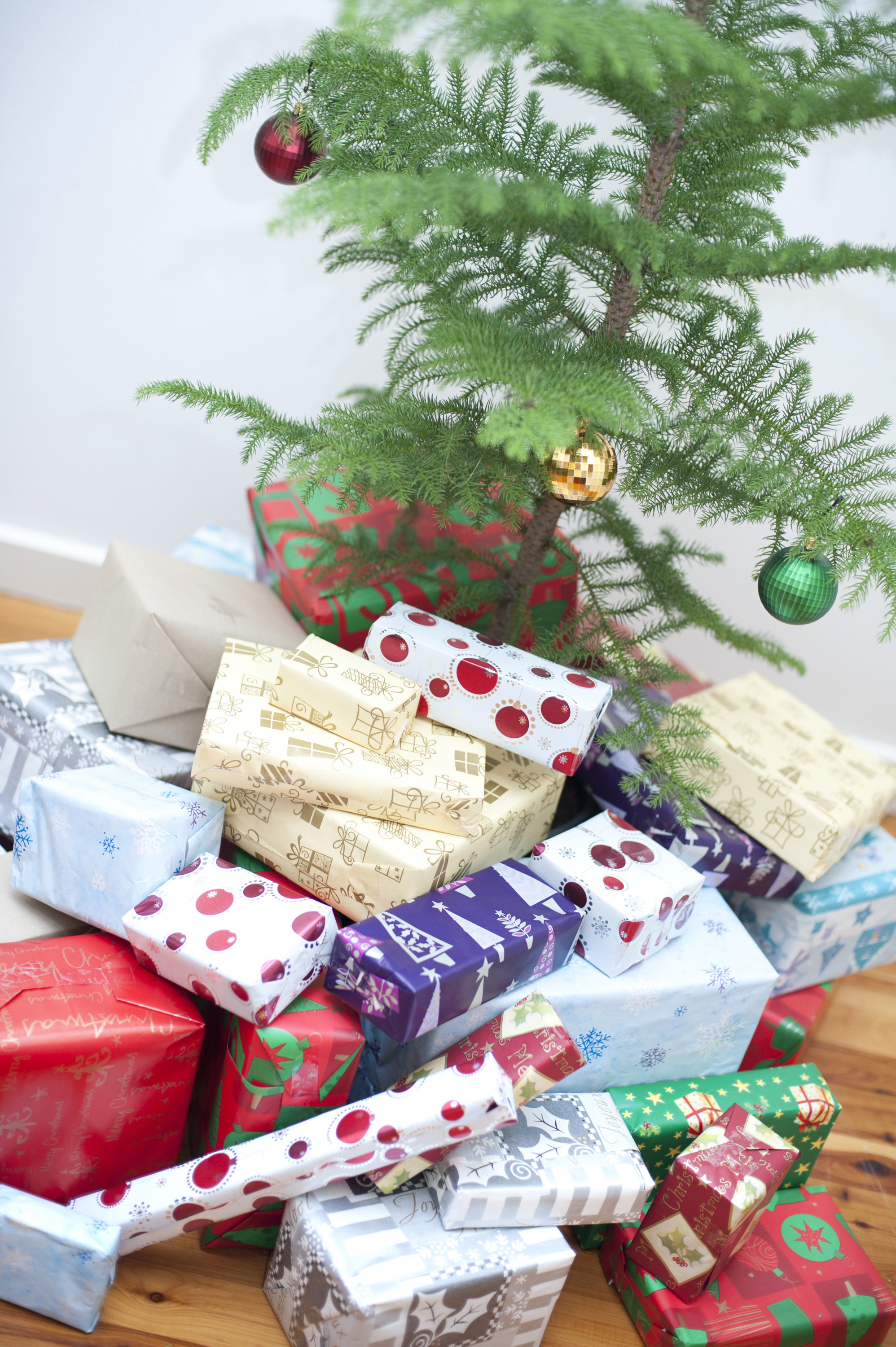 Small Simple Evergreen Christmas Tree And A Pile Of Gifts Wrapped In Traditional Colourful Patterned Gift