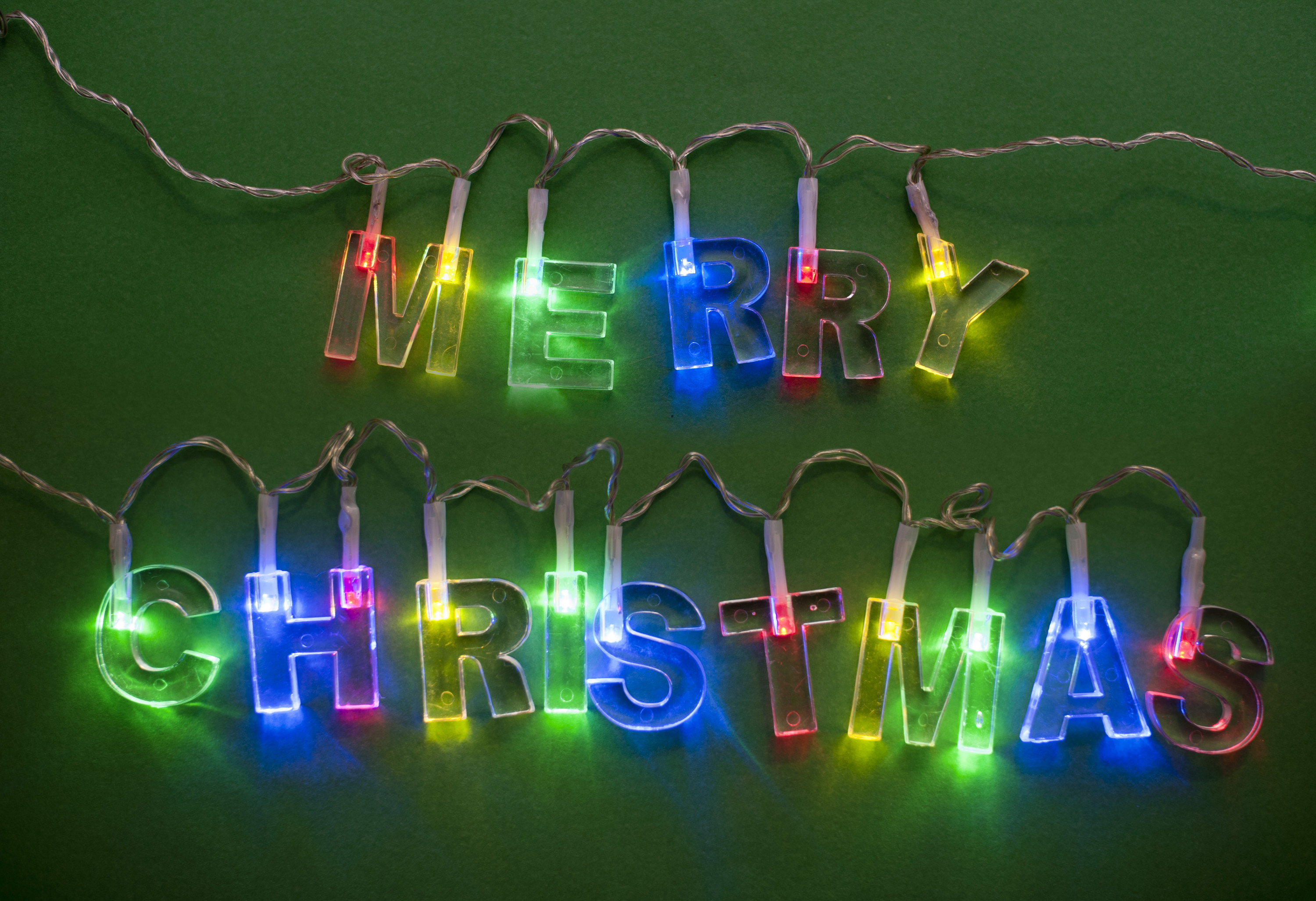 close up of lighted merry christmas garland on green background